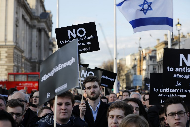 Members of the Jewish community protest against Corbyn in London on 26 March 2018 (AFP)