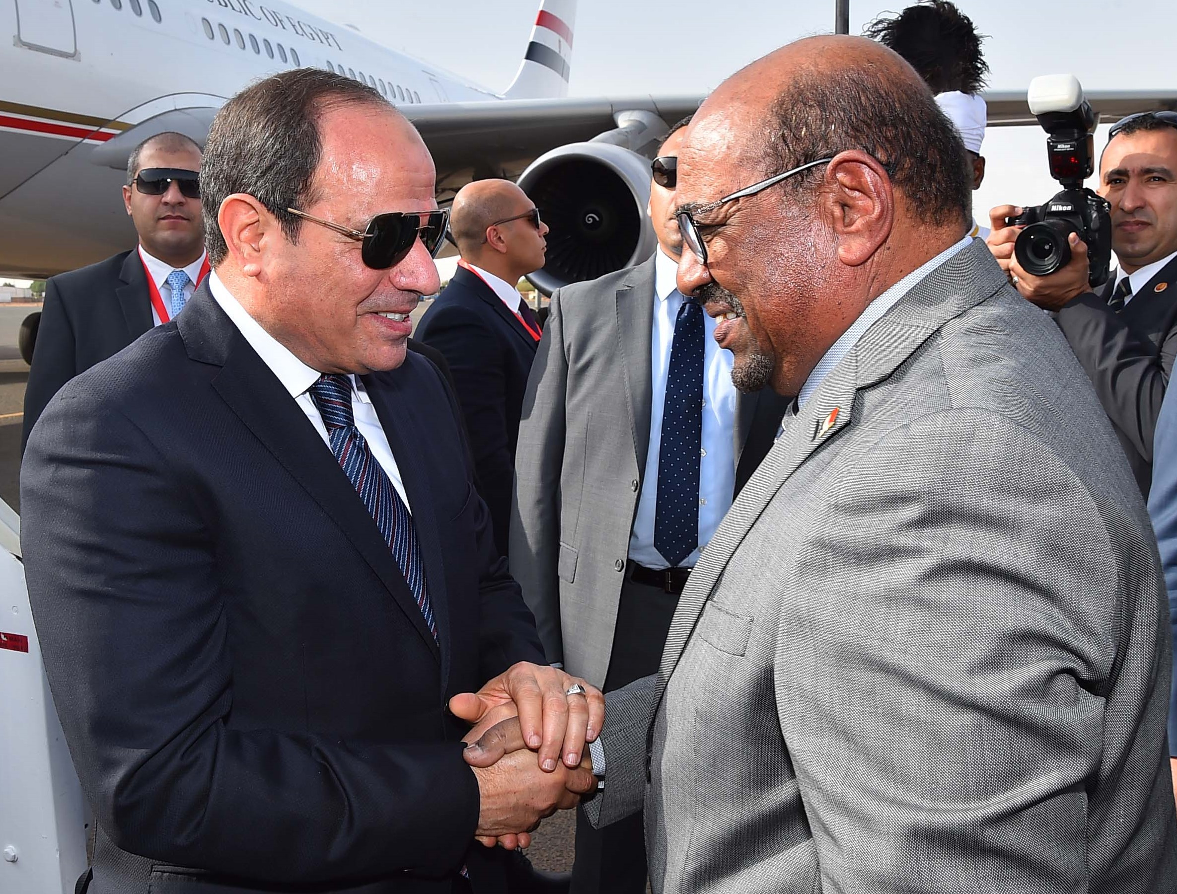 Sudanese President Omar al-Bashir (R) greeting his Egyptian counterpart Abdel Fattah al-Sisi upon his arrival at Khartoum International Airport in the Sudanese capital on 19 July 2018 (AFP)