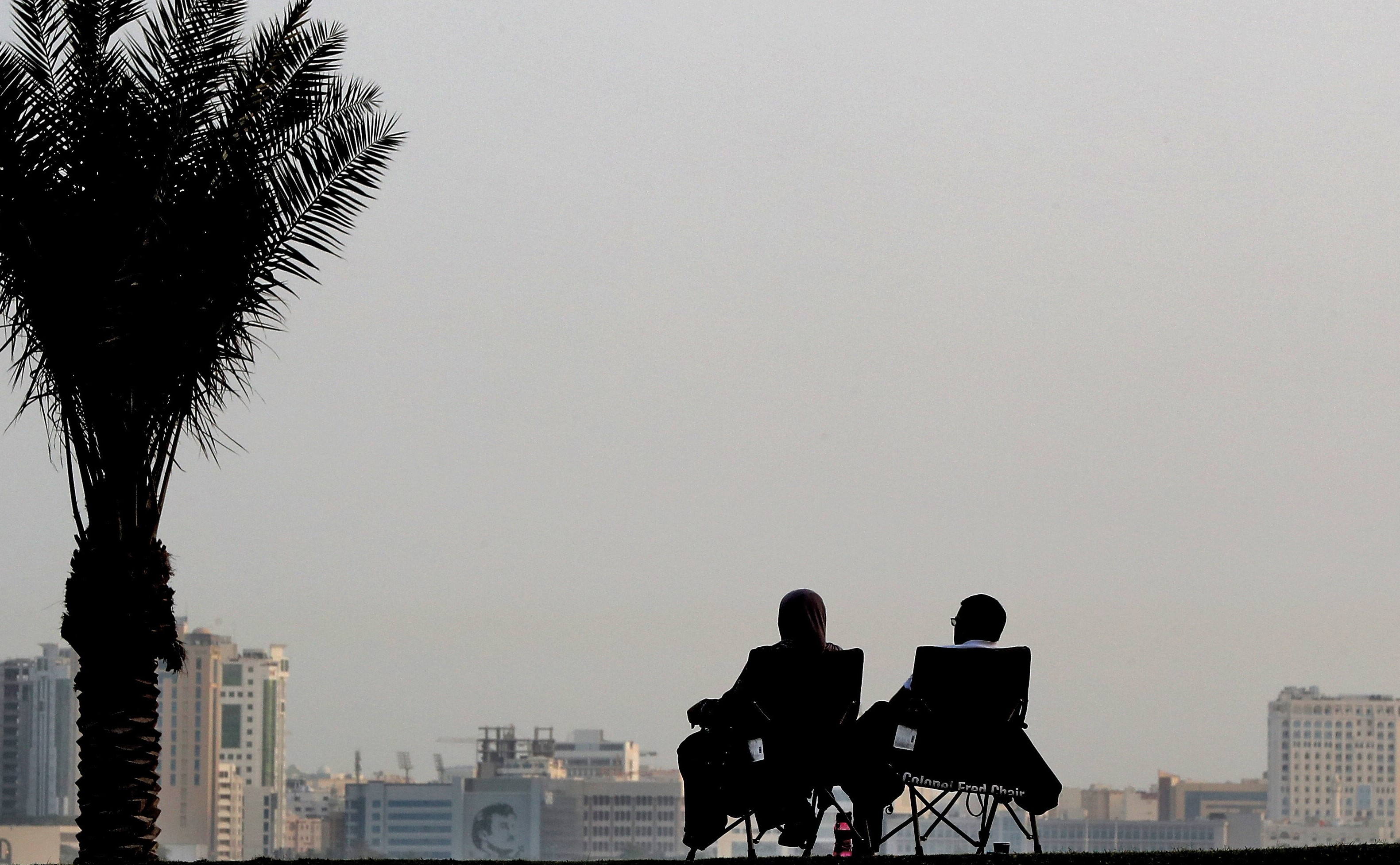 A couple sitting on Doha Corniche (AFP)