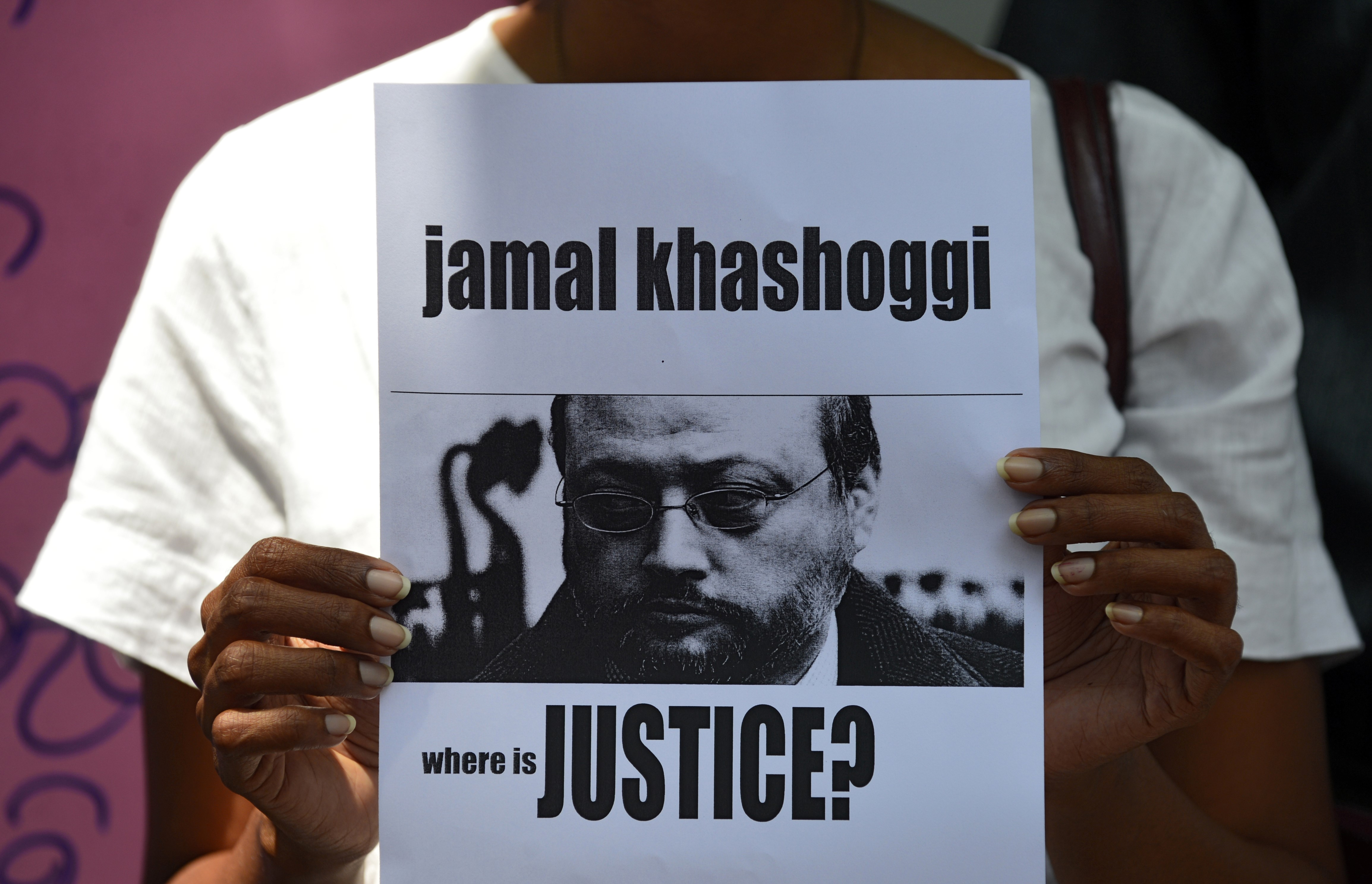 A Sri Lankan journalist holds a placard with the image of Saudi journalist Jamal Khashoggi during a demonstration outside the Saudi Embassy in Colombo on 25 October 2018 (AFP)