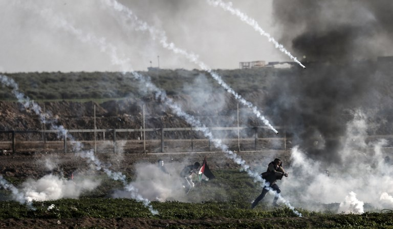 Palestinian protesters run from tear gas fired by Israeli troops in Gaza on 25 January (AFP)