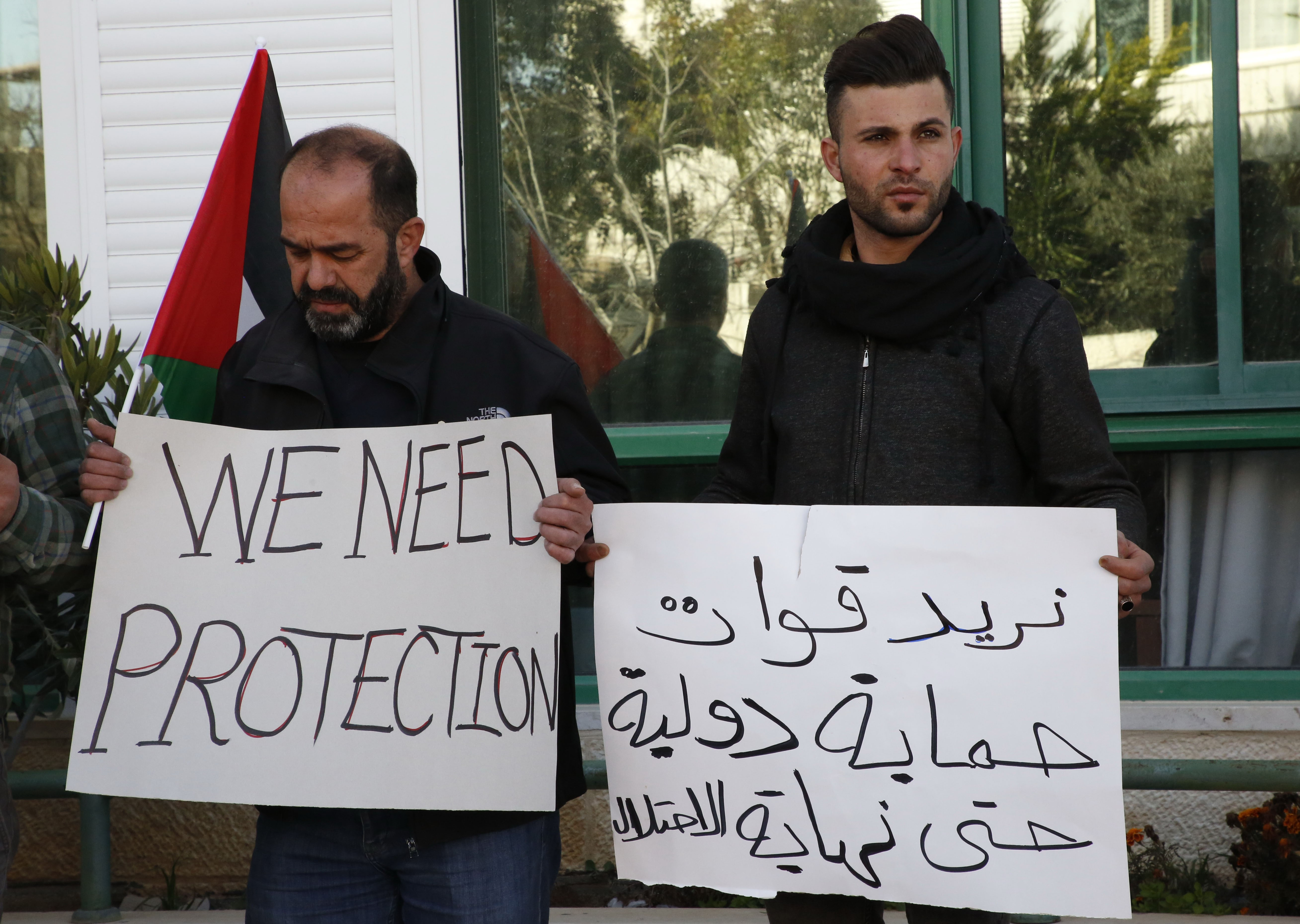 Palestinians carry placards denouncing the Israeli prime minister's recent decision not to renew the mendate of The Temporary International Presence in Hebron (TIPH) on 30 January (AFP)