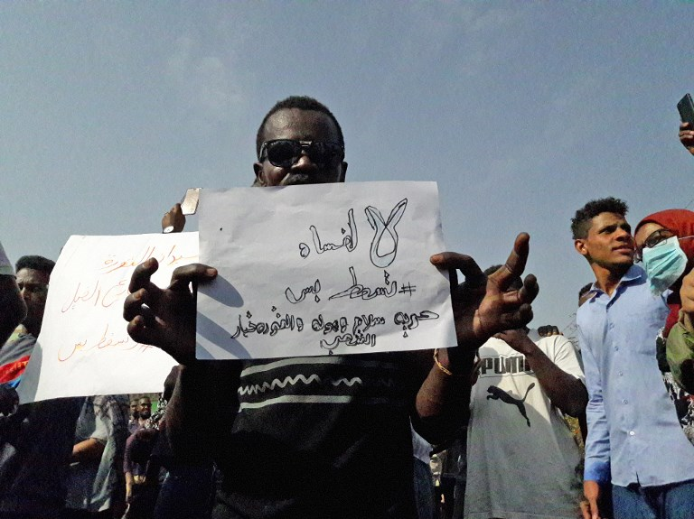 A Sudanese protester holds a placard with an anti-corruption slogan on 31 January (AFP)