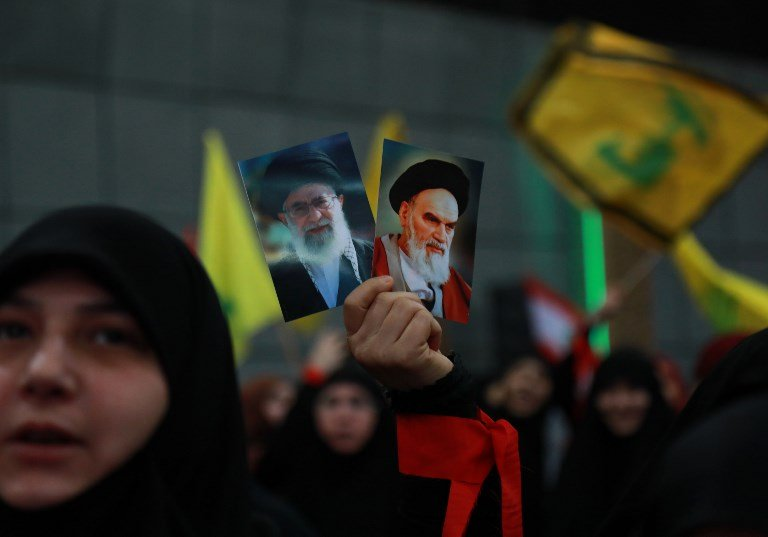 Hezbollah supporters hold images of Ayatollah Ruhollah Khomeini and Ayatollah Ali Khamenei during celebrations marking the 40th anniversary of the Iranian revolution in Beirut on 6 February (AFP)