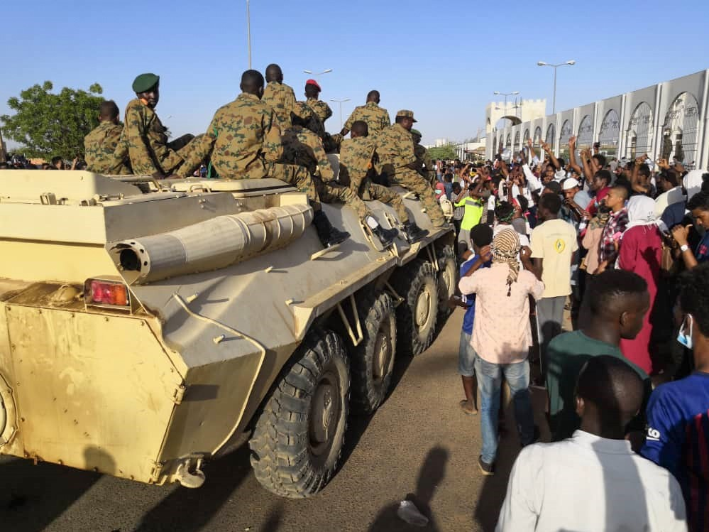 Sudanese protesters flash the victory sign at a passing military vehicle as they rally for a second day outside the military headquarters in the capital Khartoum on 7 April (AFP)