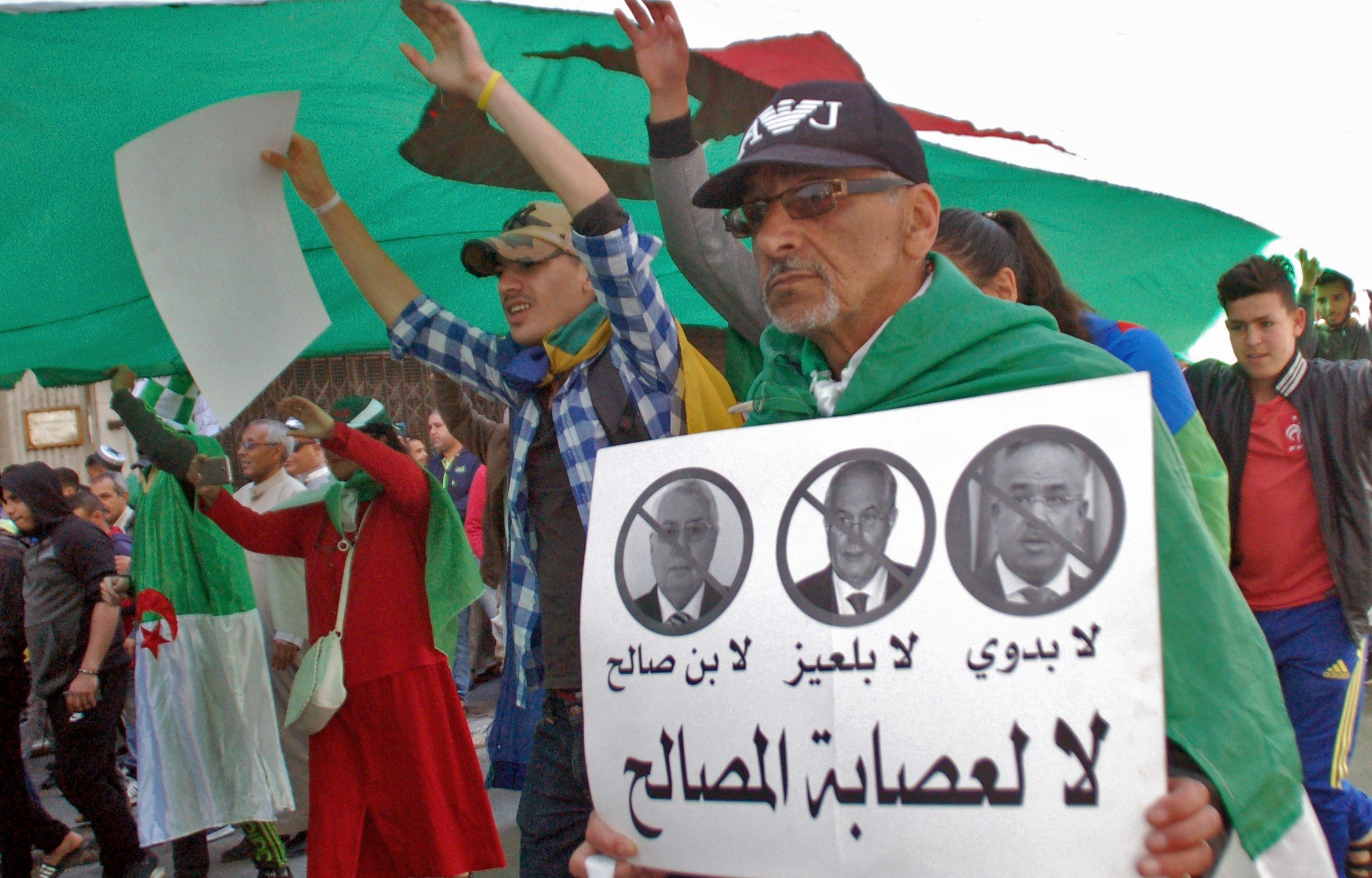 "An Algerian man marches with a sign against the ""3B"" (Interim leader Abdelakder Bensalah, constitutional council chief Tayeb Belaiz and Prime Minister Noureddine Bedoui)in the city of Oran on 9 April (AFP)"