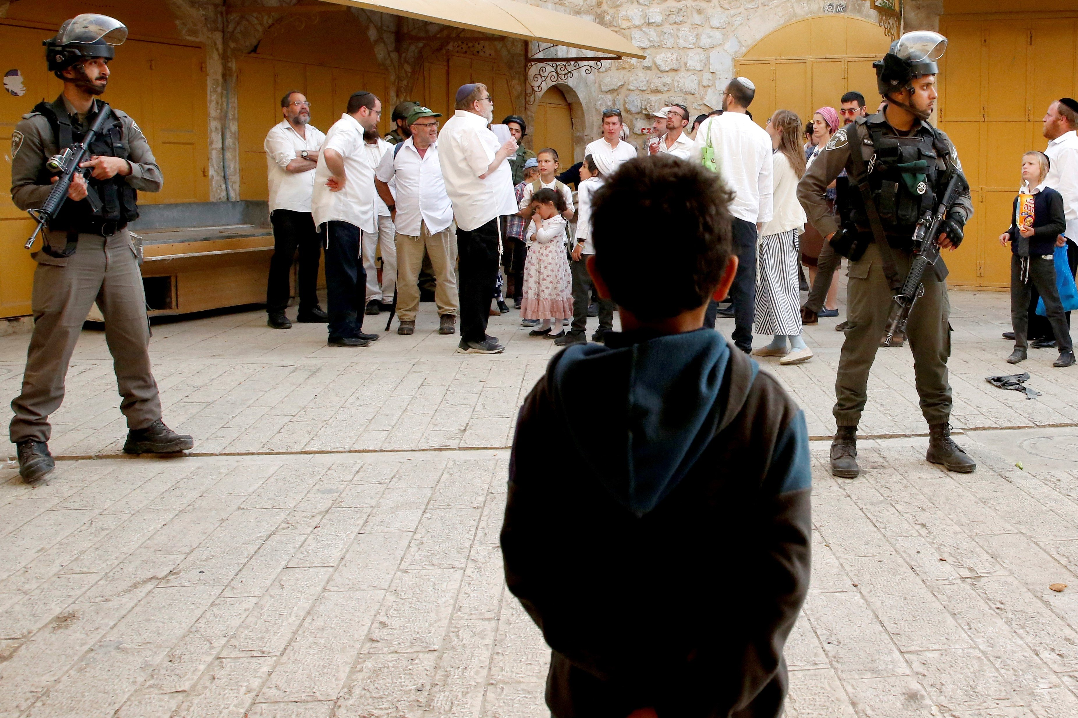 A Palestinian child looks at Israeli soldiers standing guard as settlers stroll through the market in Hebron on 13 April (AFP)