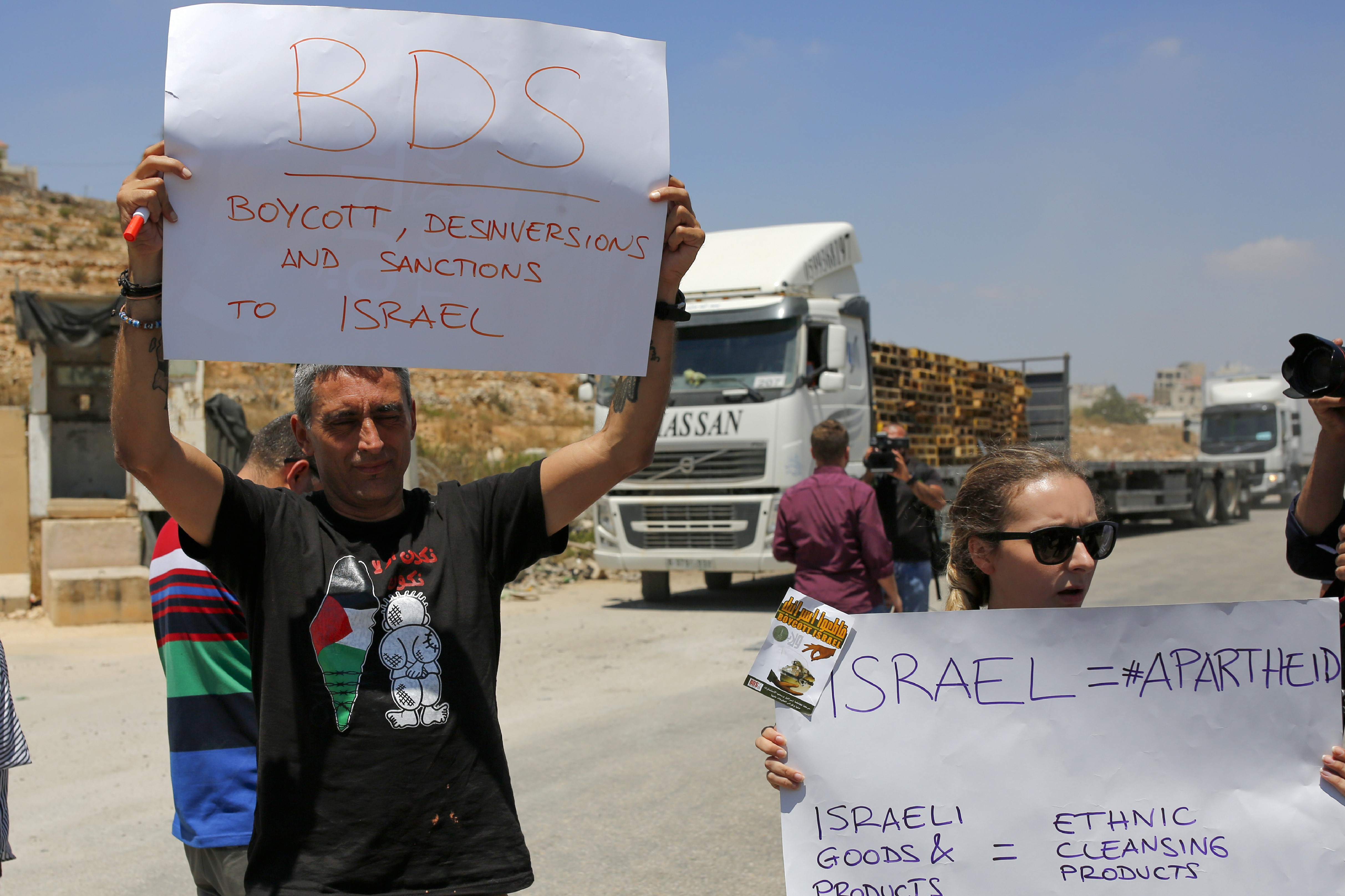 Palestinians demonstrate at the Ofer Israeli checkpoint near Ramallah, calling on Palestinians to boycott Israeli goodson 6 August (AFP)