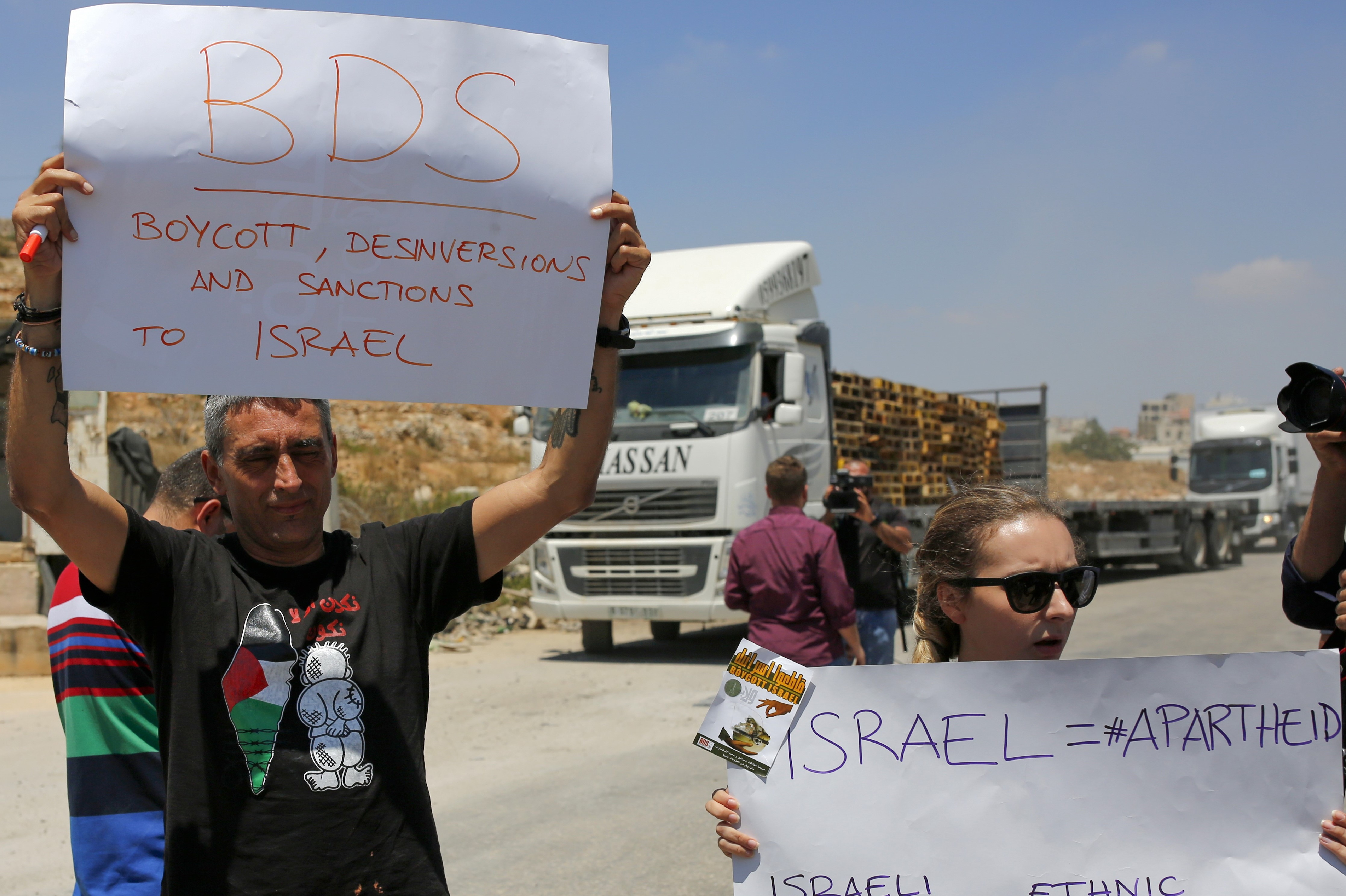 Palestinians demonstrate at the Ofer Israeli checkpoint near Ramallah, through which Israeli goods are usually transported to the West Bank, calling on Palestinians to boycott such imports, on August 6, 2019