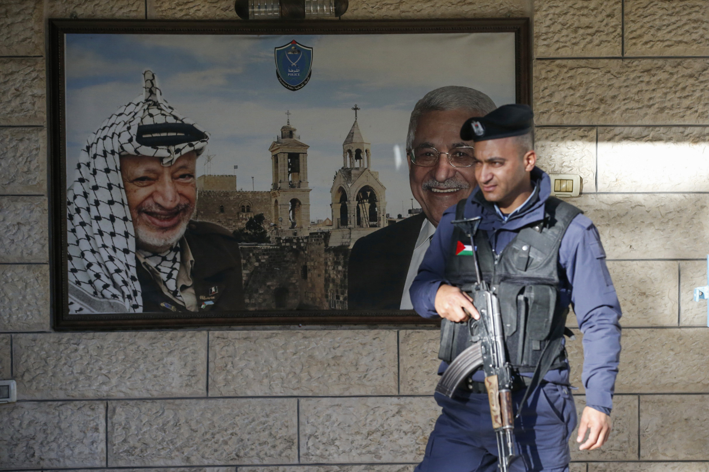 A Palestinian policeman stands guard in front of a poster bearing the portraits of late Palestinian leader Yasser Arafat (L) and Palestinian president Mahmoud Abbas at the Church of the Nativity on 24 December, 2019 (AFP)