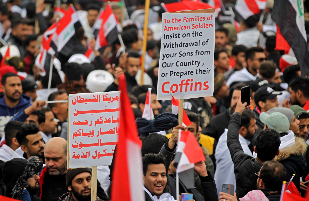 "Protesters raise placards as supporters of Iraqi cleric Moqtada Sadr gather in the capital Baghdad for a ""million-strong"" march to demand an end to the presence of US forces in their country (AFP)"