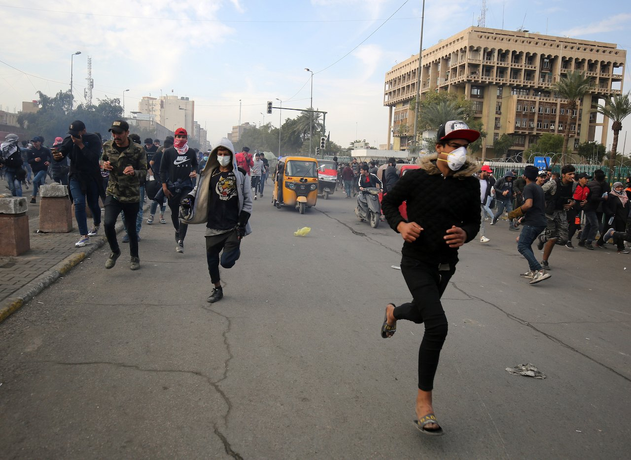 Iraqi protesters run for cover during clashes with riot police following a demonstration in Al-Khilani Square in the capital Baghdad (AFP)