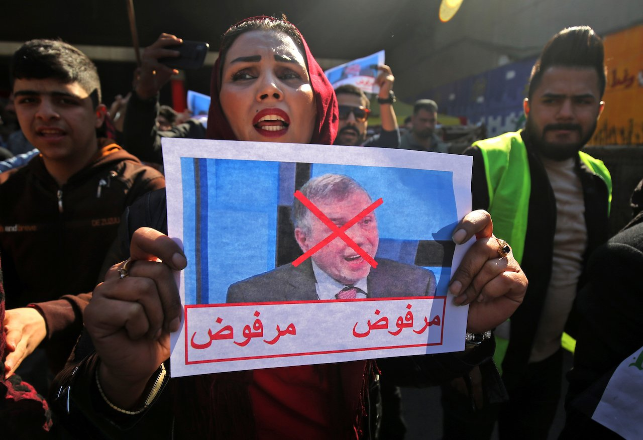 "An Iraqi protester lifts pictures of the premier-designate Mohammad Allawi with the inscription ""rejected"", during an anti-government demonstration the capital Baghdad's Tahrir square (AFP)"