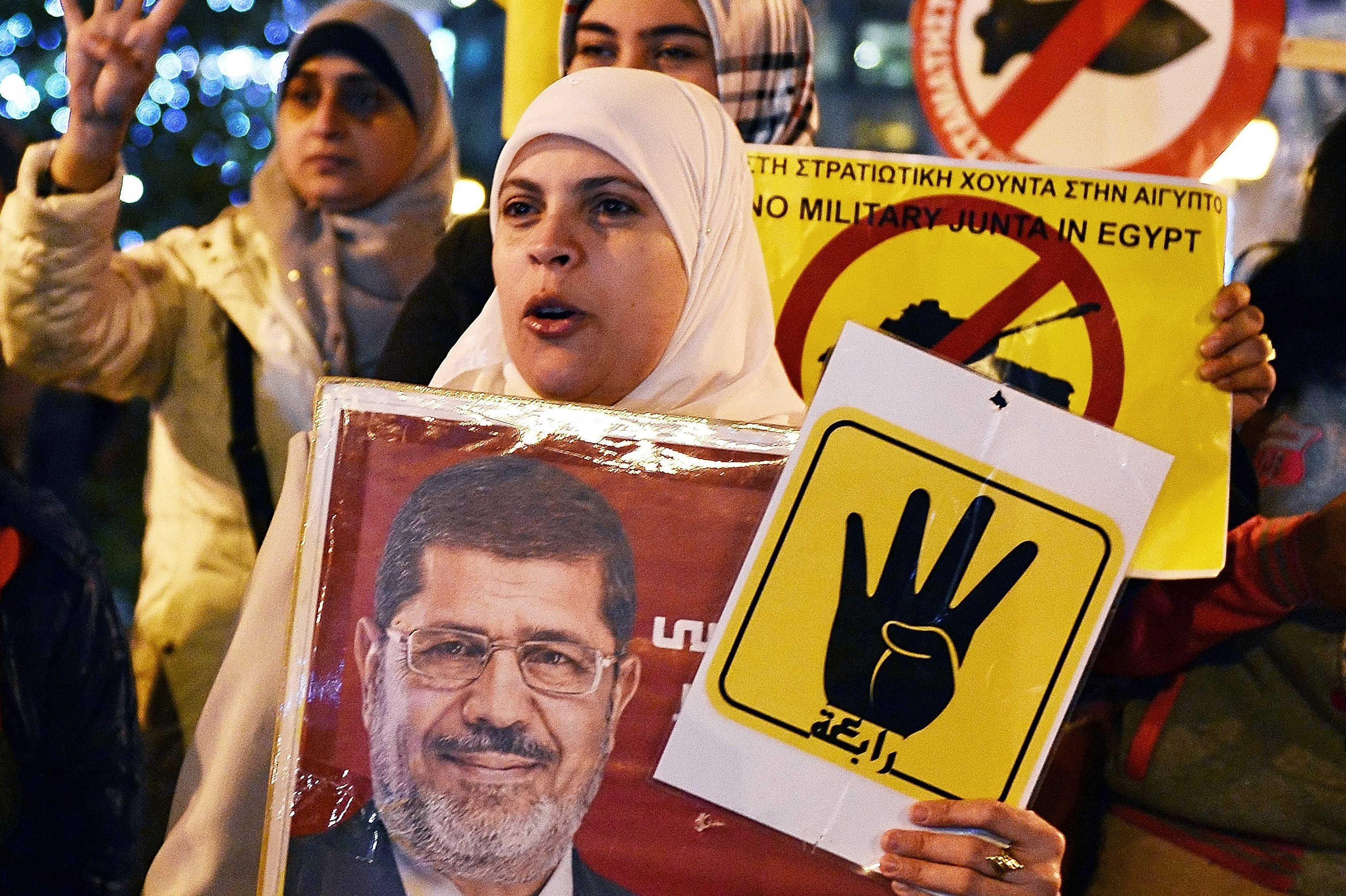 A woman holds up a banner of former Egyptian President Mohamed Morsi in anti-Sisi protest in Athenes in December 2015 (AFP)