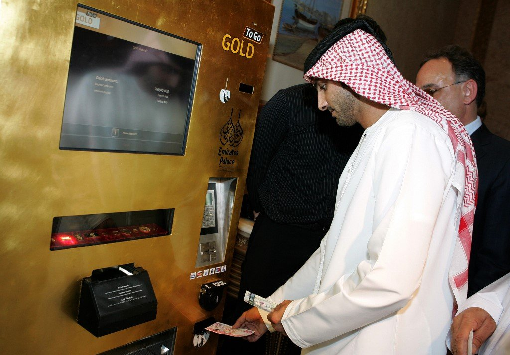 "An Emirati man tries the ""Gold to Go"" vending machine at the Emirates Palace Hotel in Abu Dhabi in May 2010"