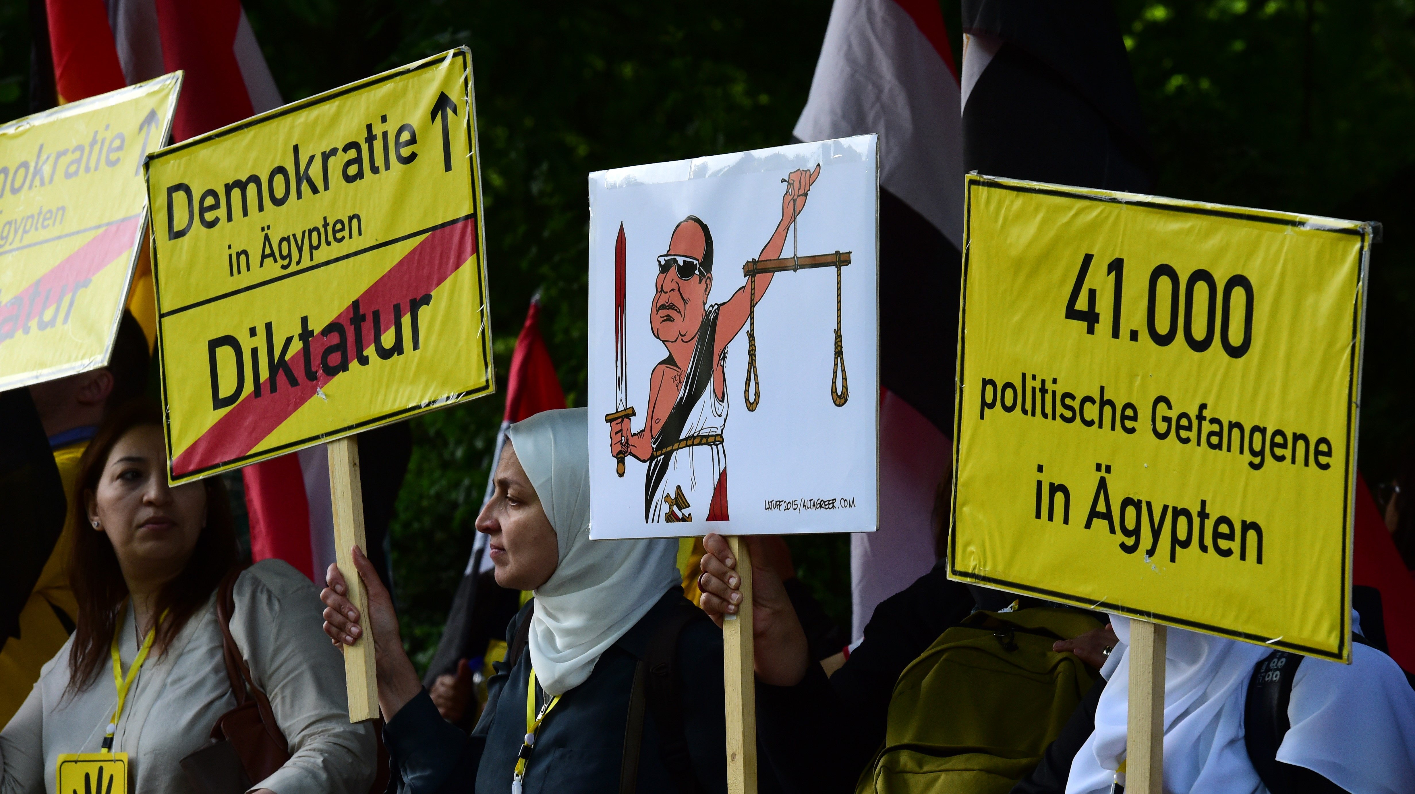 "Protesters hold banners reading ""Democracy in Egypt- Dictatorship"" prior arrival of Egyptian President Abdel Fattah al-Sisi for the meeting with German President in front of Schloss Bellevue castle on 3 June, 2015 in Berlin (AFP)"