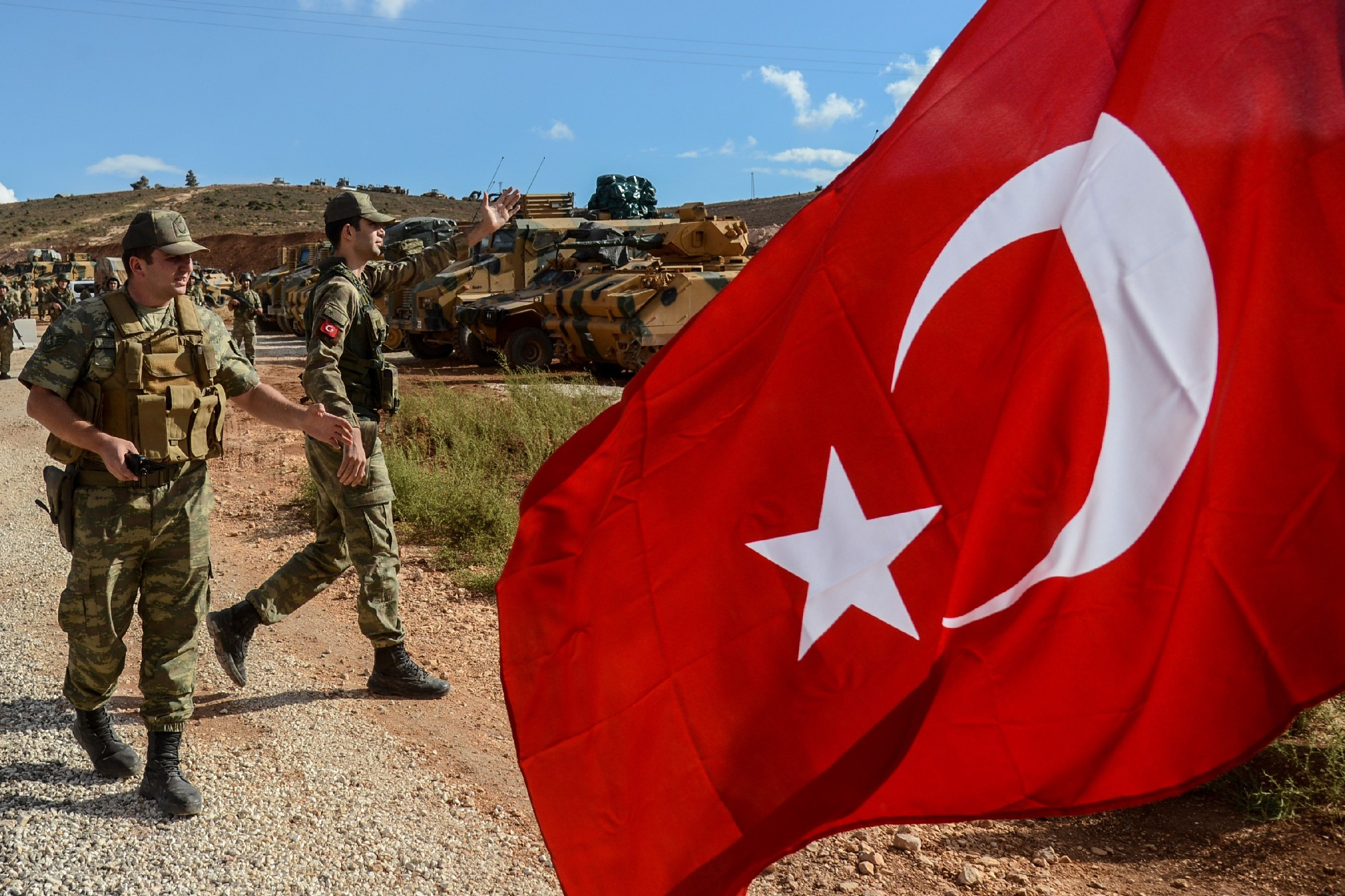 Turkish soldiers stand near armoured vehicles near the Turkey-Syria border near Reyhanli, Hatay, on 10 October, 2017 (AFP)