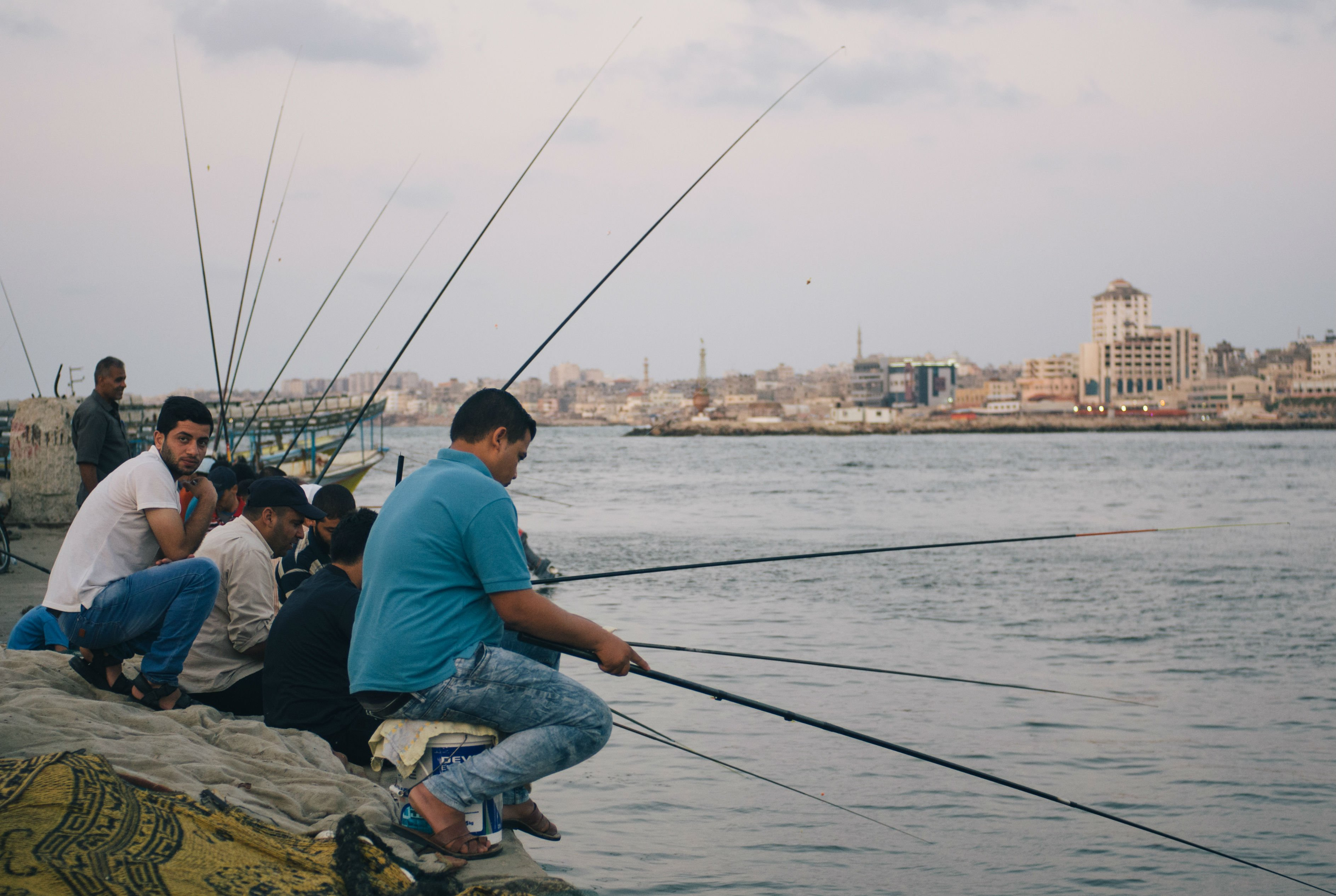 Palestinian men sit together at Gaza's port when they don't have work, which is often for the enclave's many unemployed, drinking coffee as they watch their rods