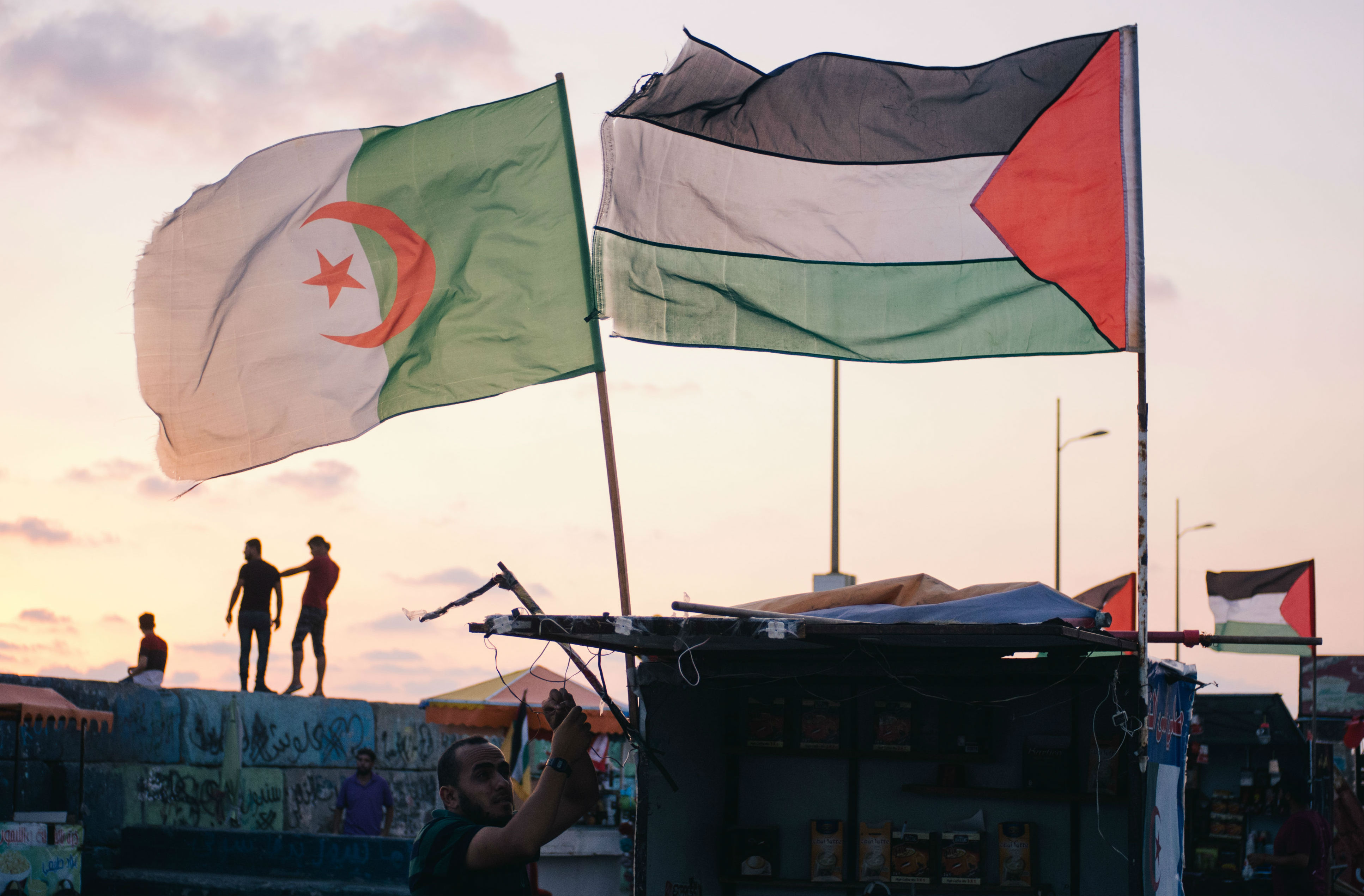 A vendor sets up his coffee stall decorated with the Algerian flag, catering for the families who whittle away the evening hours in the port. Palestinian youths climb up the breeze blocks behind him, posing for selfies against the sunset