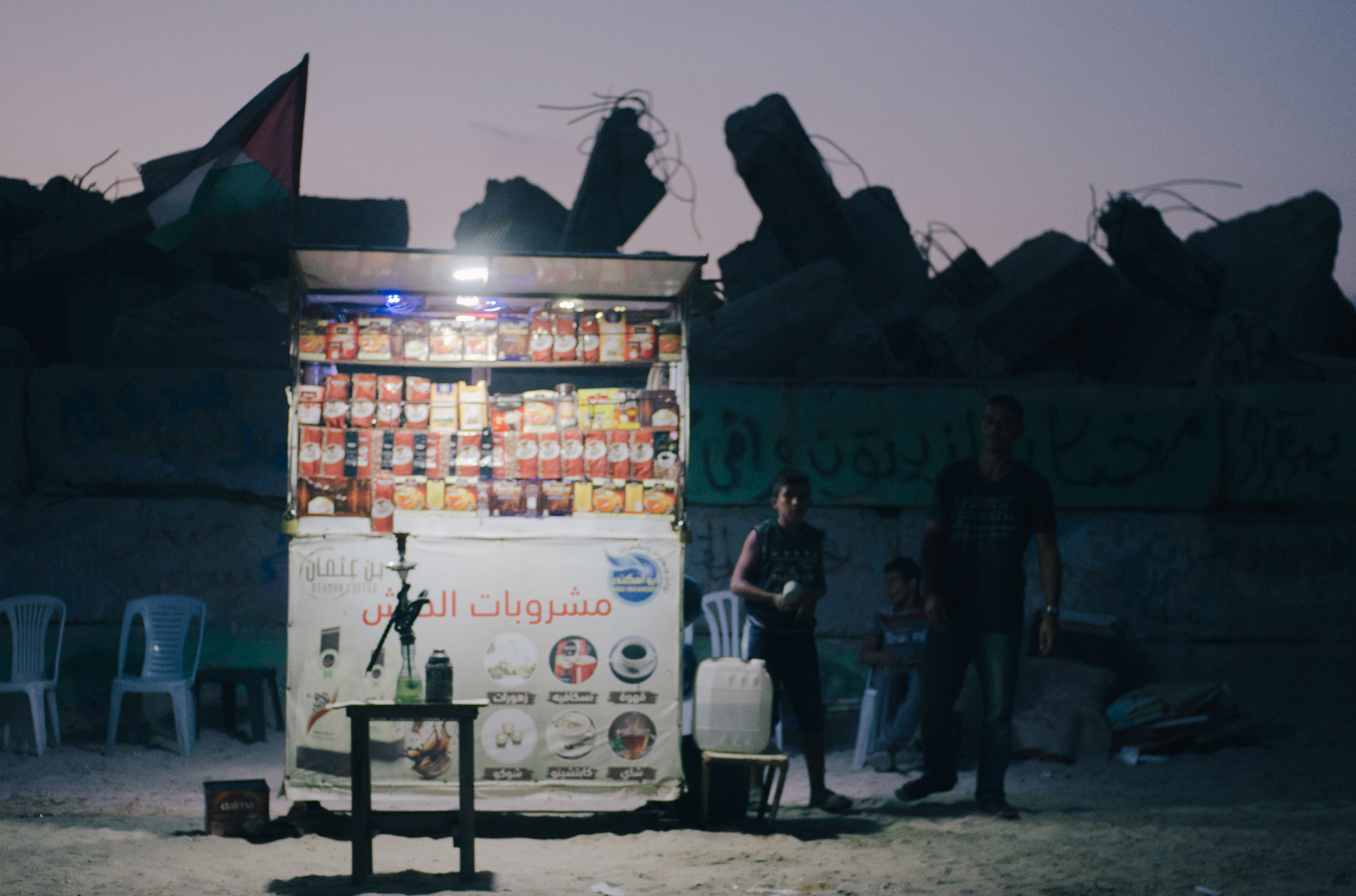 As the sun sets on Gaza, little pinpricks of light begin dotting the darkened coastline. Battery-powered LEDs fastened to coffee stalls cut against the night in the power-starved enclave, the only source of illumination for teen vendors preparing for nightly gatherings by the sea