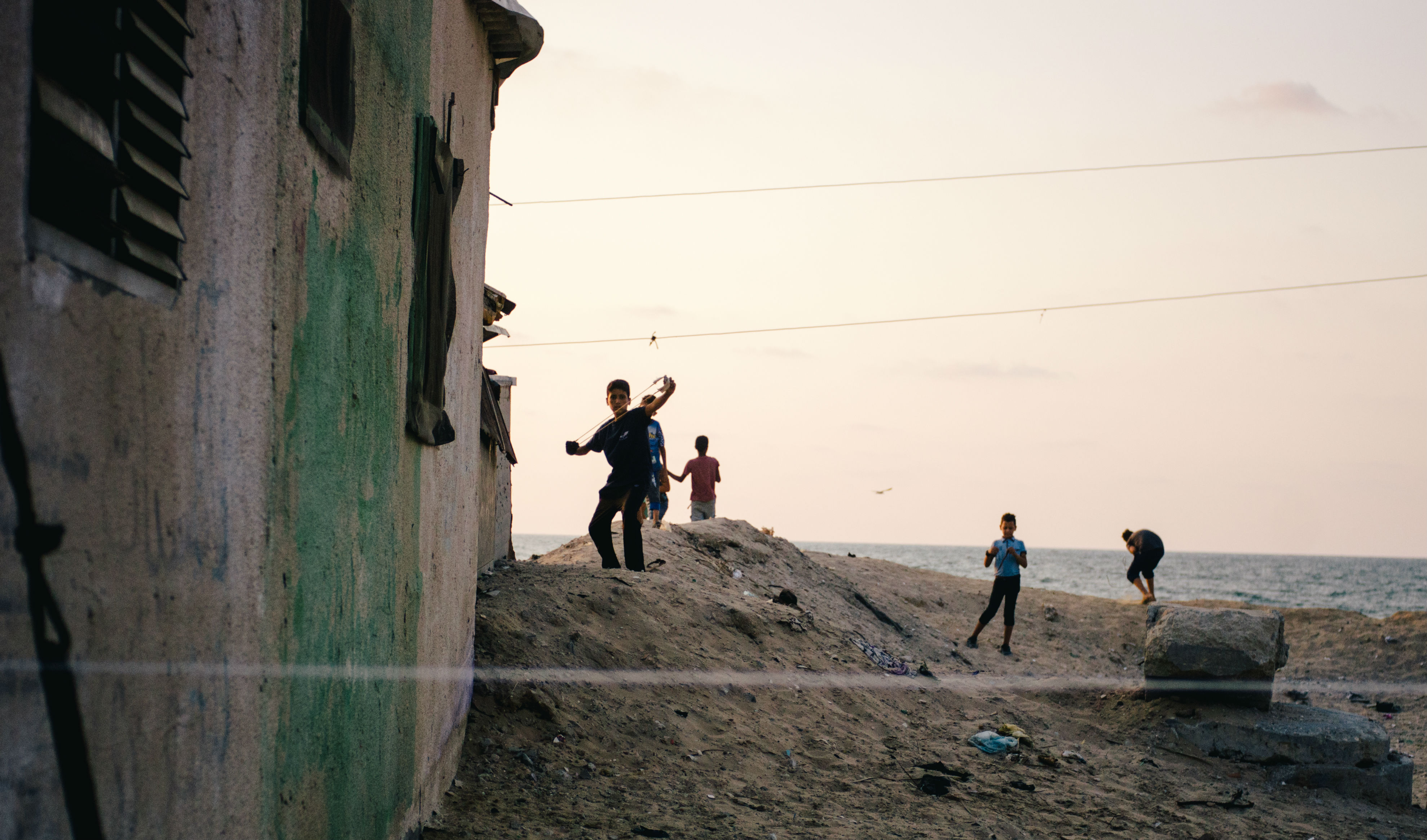 As the men and older teens weave the ropes for fishing nets, Shati camp's kids play on the shore, flinging stones into the Mediterranean with their sling shots. Only metres away a wastewater pipe pumps sewage into the sea