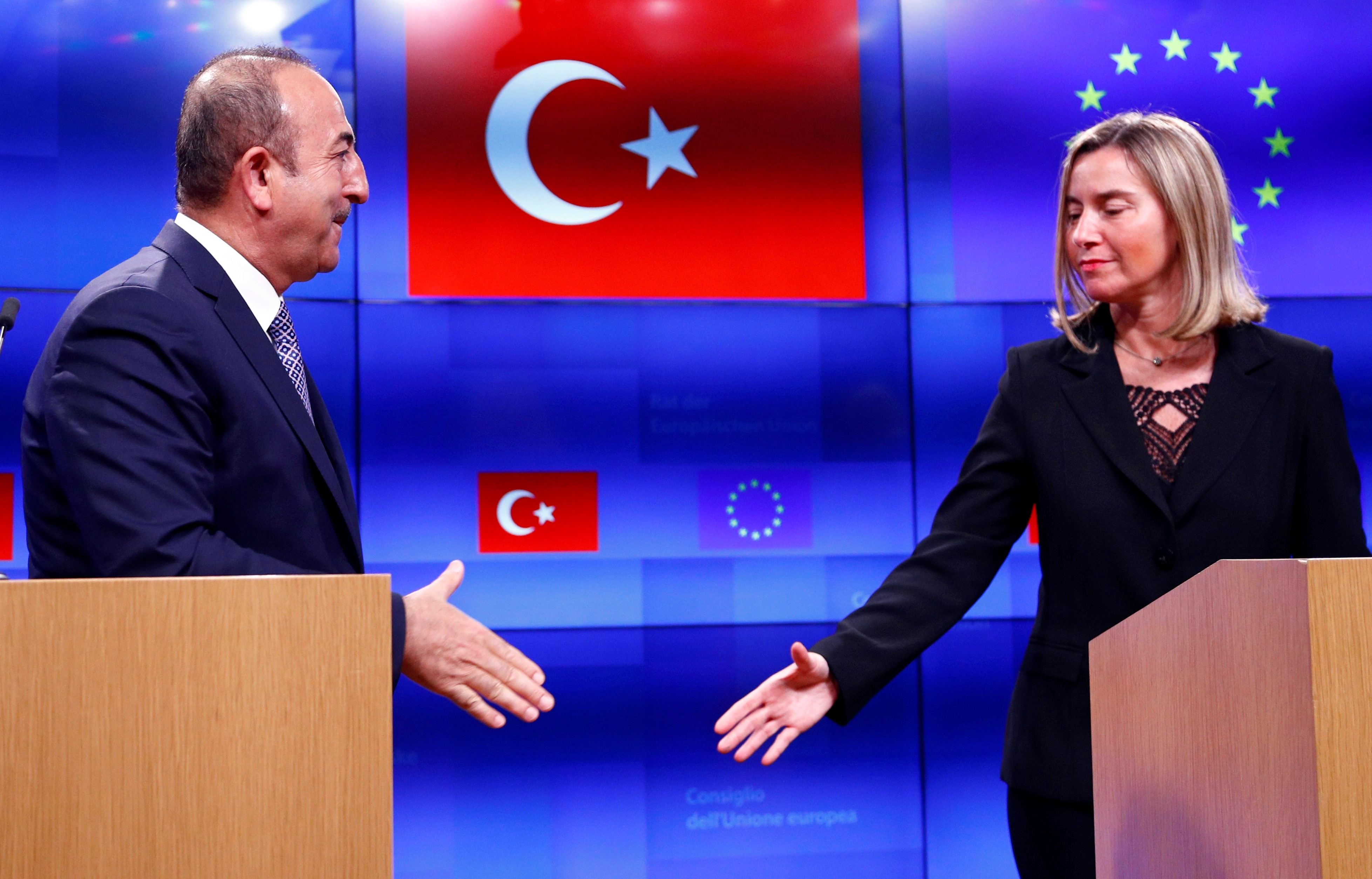 Turkish Foreign Minister Mevlut Cavusoglu shakes hands with European Union foreign policy chief Federica Mogherini  Belgium on 15 March (Reuters)