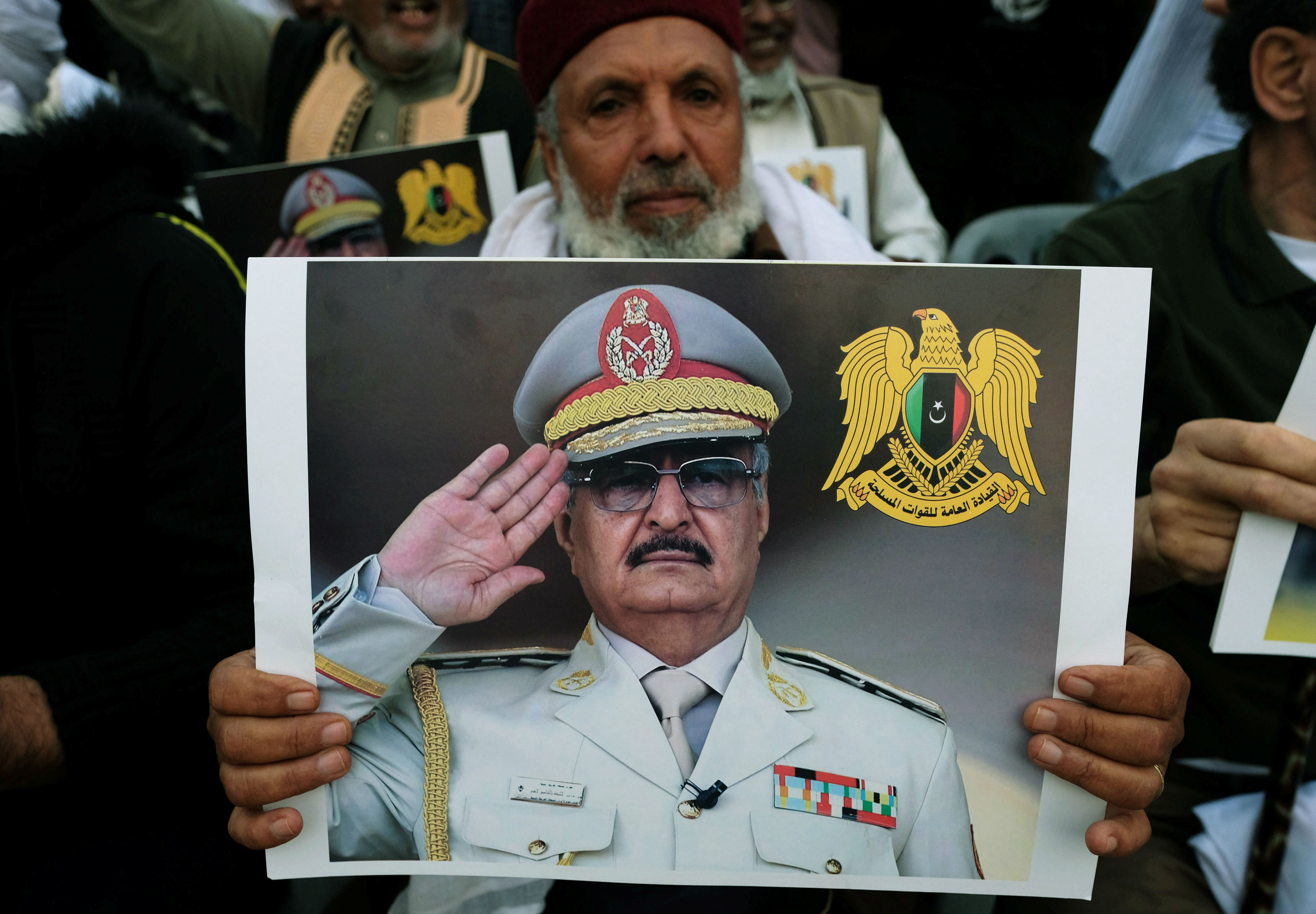 A Libyan man carries a picture of Khalifa Haftar during a demonstration to support Libyan National Army offensive against Tripoli, in Benghazi (Reuters)