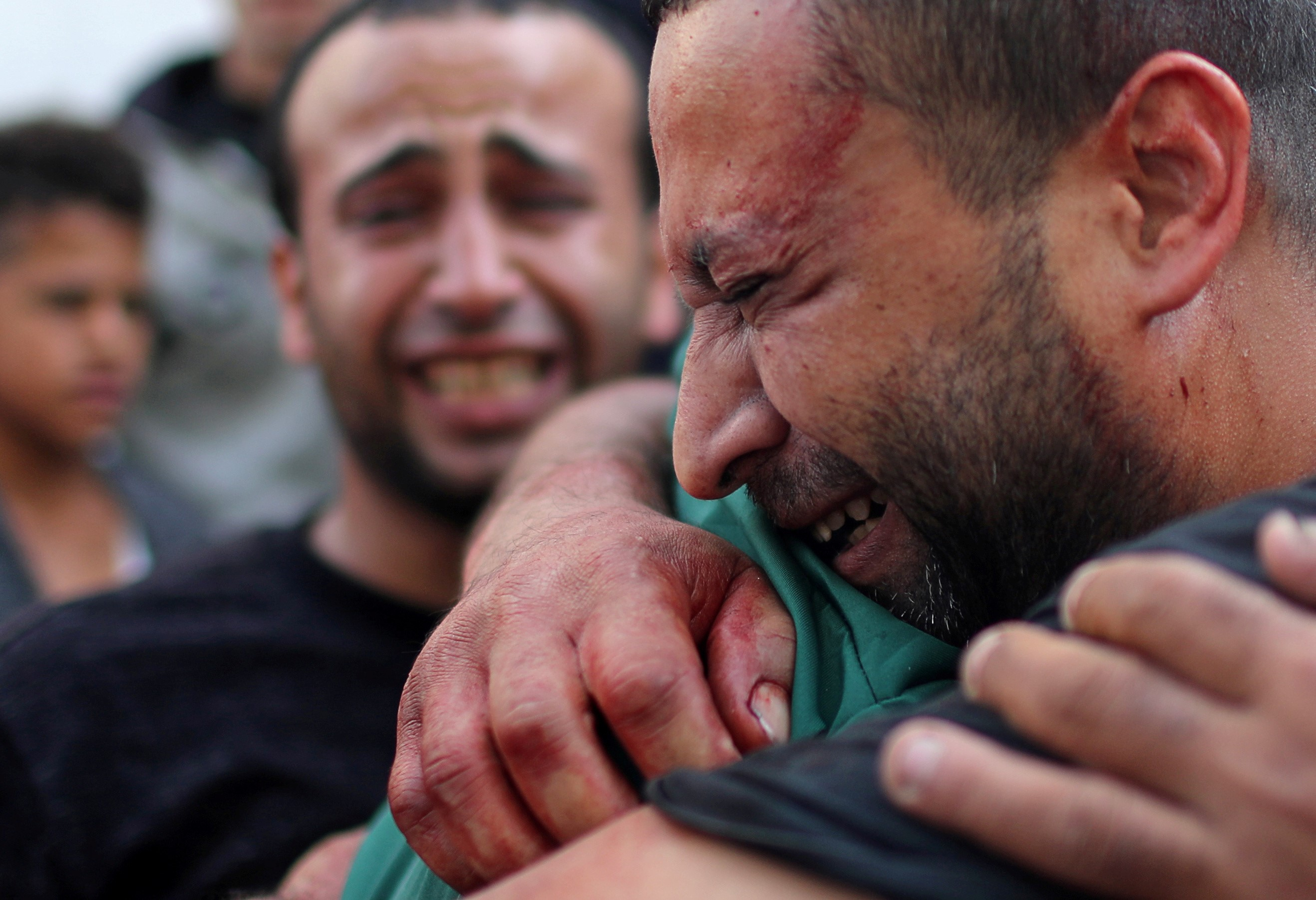 A Palestinian man, stained with the blood of his relative, is comforted as he reacts at Shifa hospital in Gaza City on 13 November (Reuters)