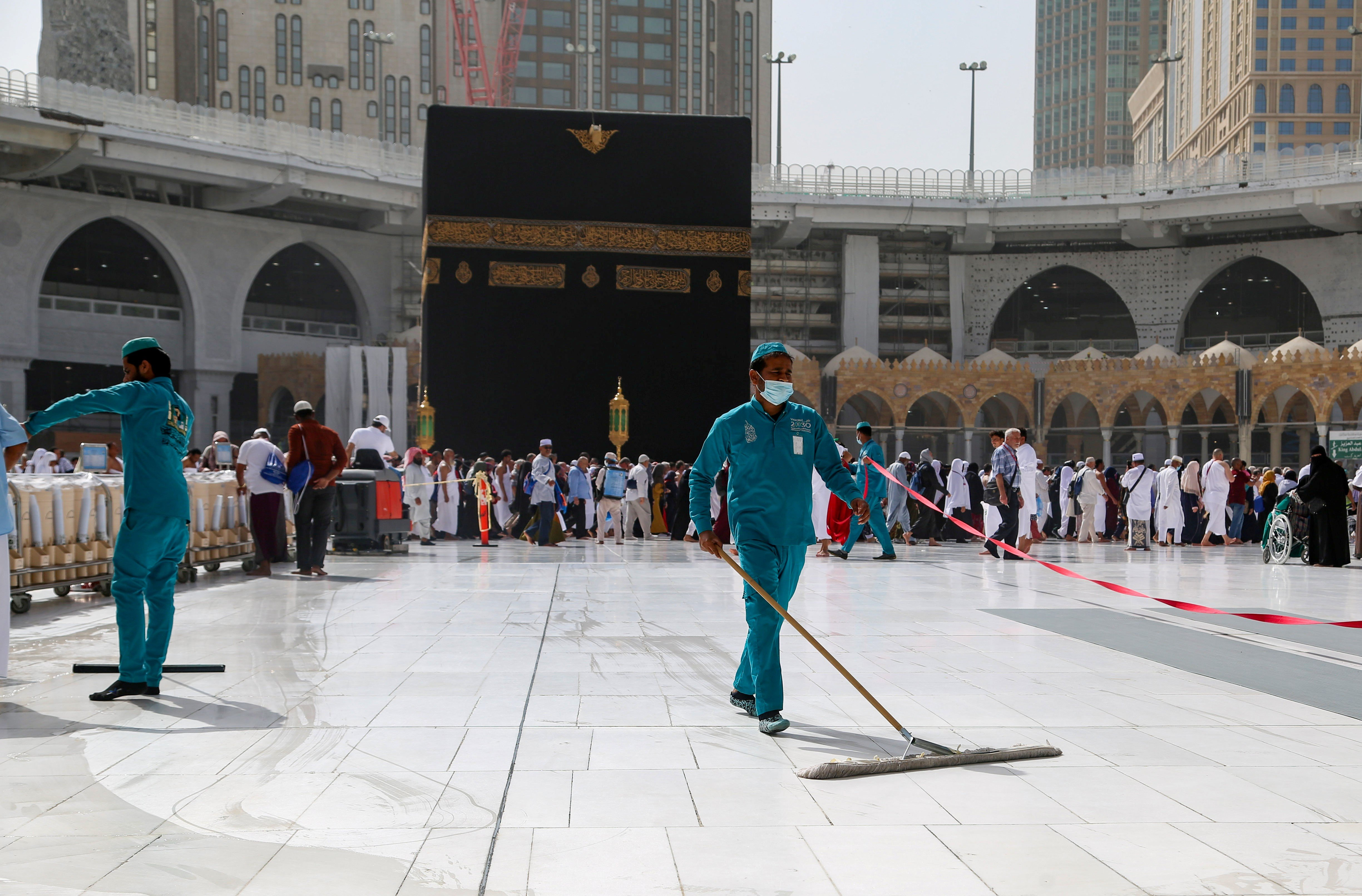 Cleaners wear protective face masks, following the outbreak of the coronavirus, as they swipe the floor at the Kaaba in the Grand mosque in the holy city of Mecca, Saudi Arabia March 3, 2020.