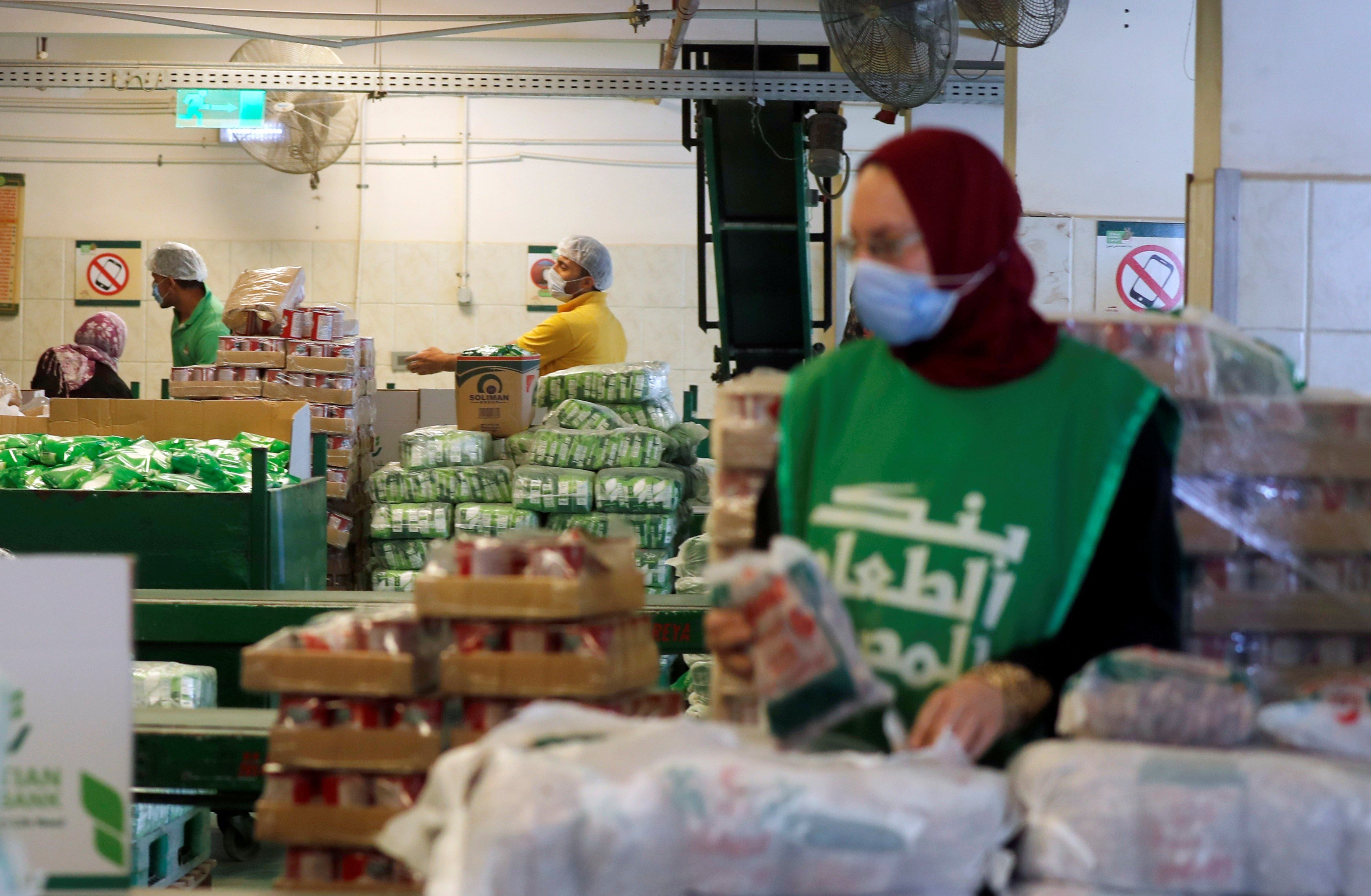 Workers of the Egyptian Food Bank fill boxes with food and aid for needy families