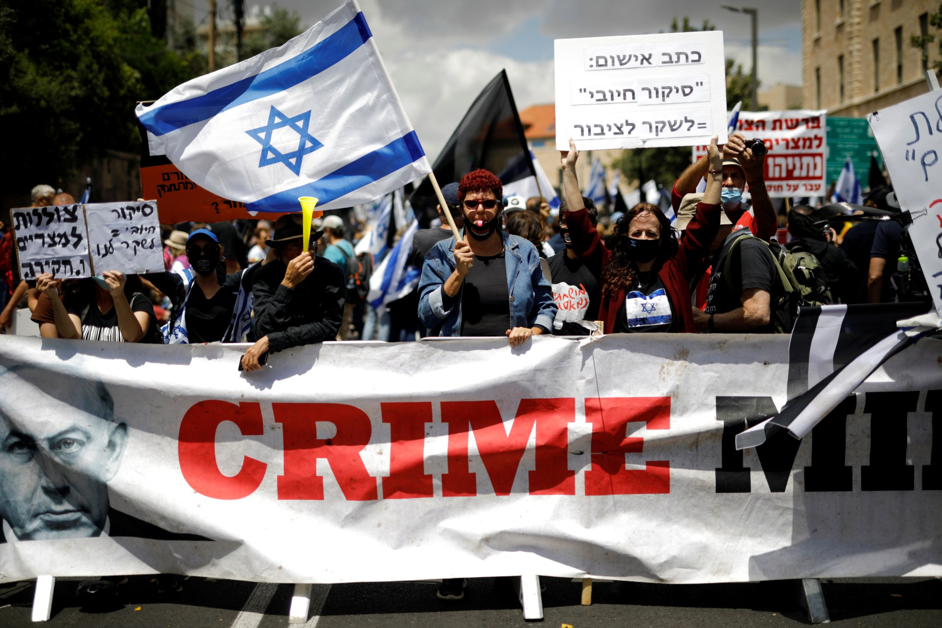 "Protesters wave an Israeli flag and hold placards as they stand behind a banner reading, ""Crime Minister"" and demonstrate against Israeli Prime Minister Benjamin Netanyahu (Reuters)"