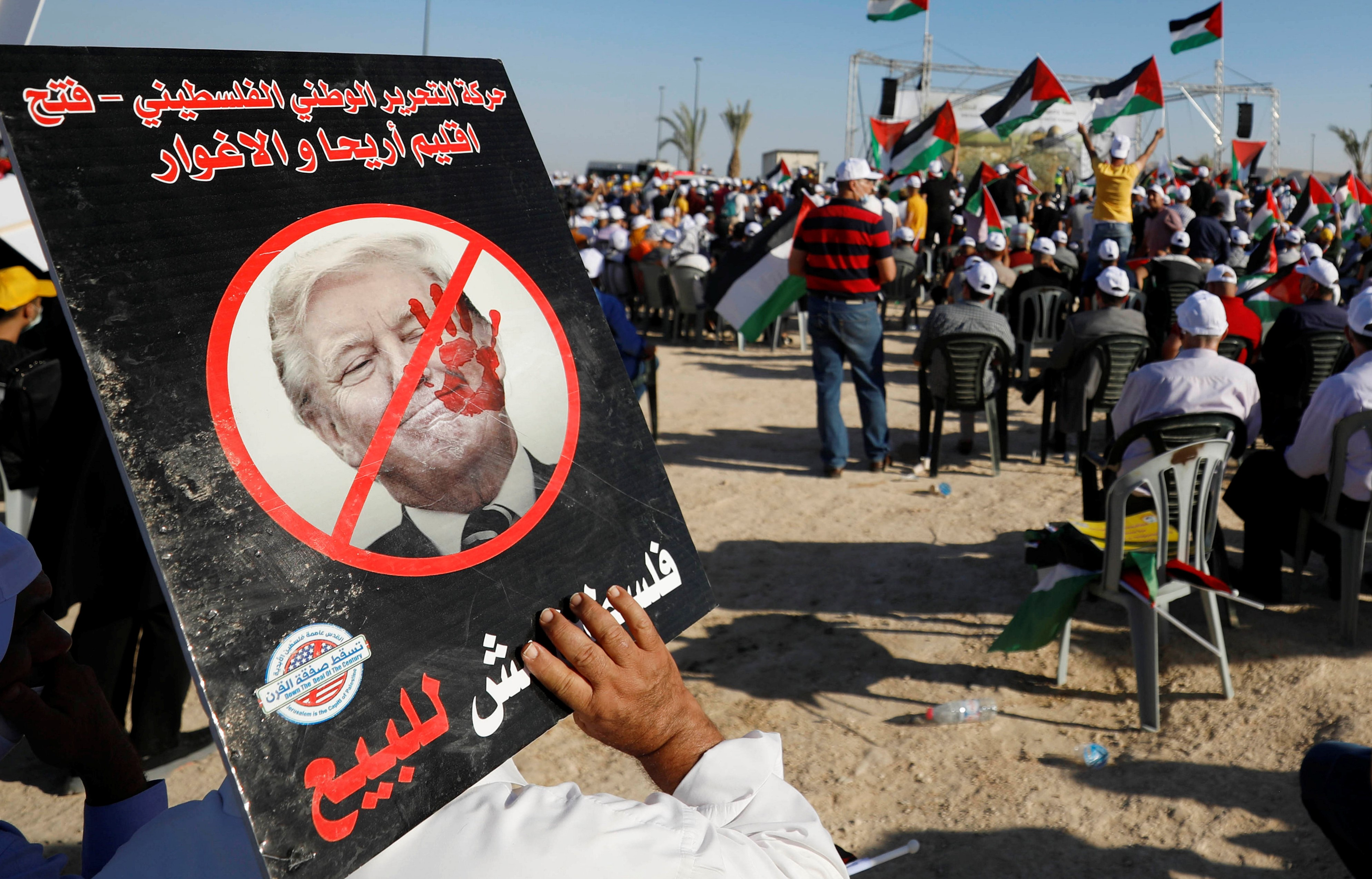 A demonstrator holds an anti-U.S. President Donald Trump placard during a rally, organised by the Palestinian Liberation Organization (PLO), to protest against Israel's plan to annex parts of the occupied West Bank, in Jericho June 22