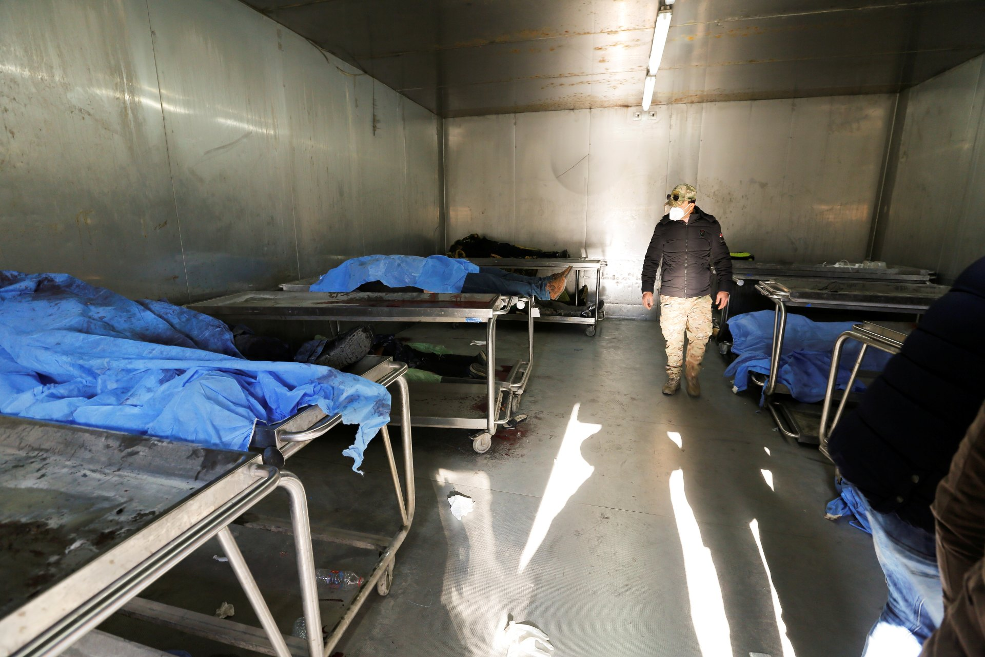 A man looks at the covered bodies of people who were killed during a twin suicide bombing attack in a central Baghdad market, at the al-Kindi hospital morgue in Baghdad (Reuters)