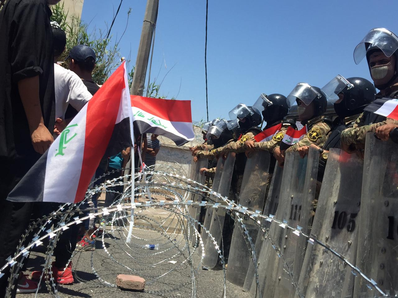 Iraqi security force prevent protesters coming close to a governmental building in Basra (Azhar Al-Rubaie)