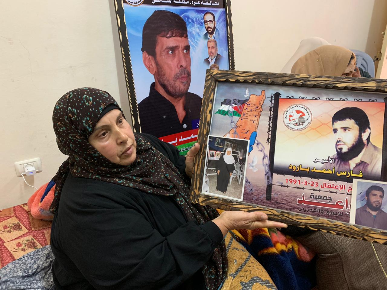 Faris Baroud's sister holds a picture of him and their mother (MEE/Hind Khoudary)