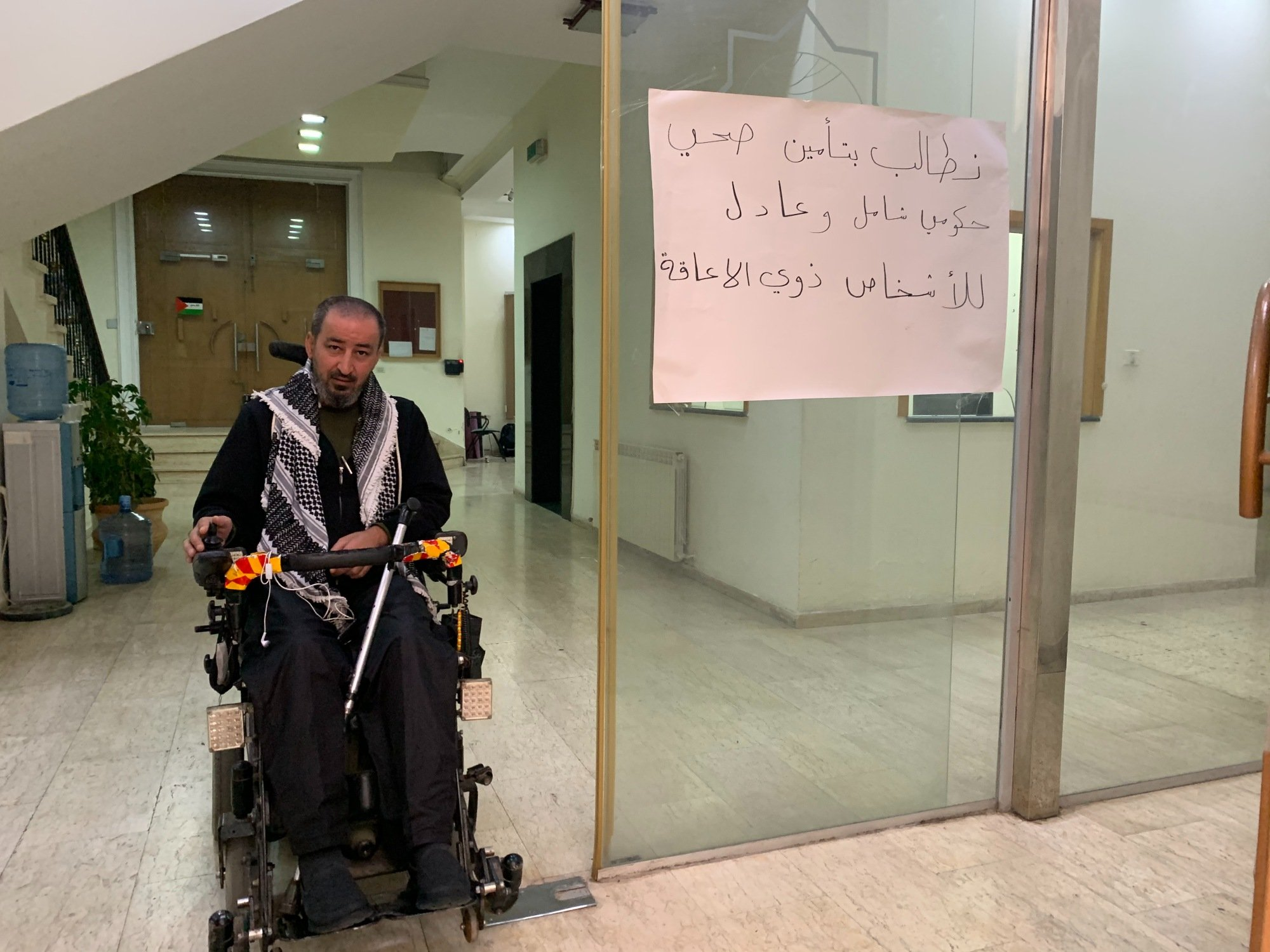 "Activists have displayed signs reading ""We demand government health care that is full and fair for people with disabilities"" (MEE/Shatha Hammad)"
