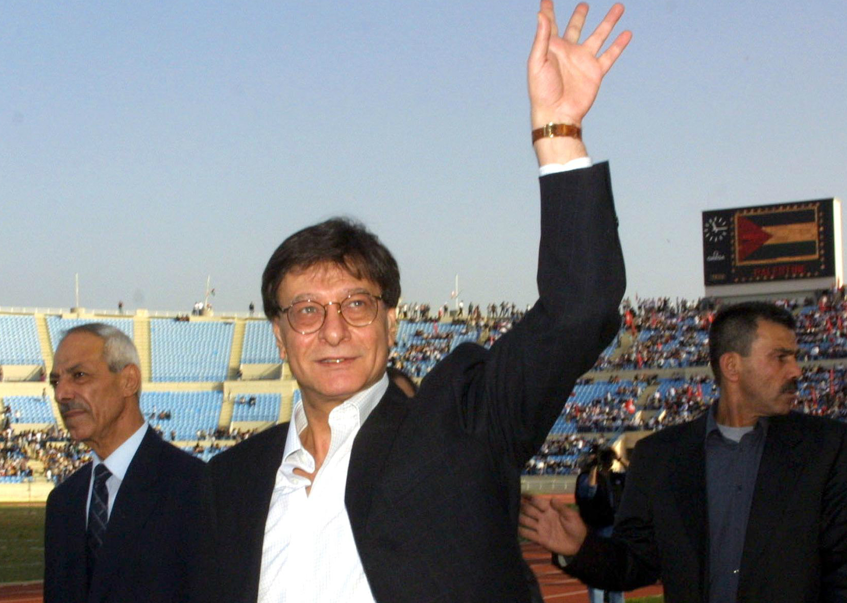 Palestinian poet Mahmoud Darwish waves to crowds before a concert and poetry reading in Beirut in April 2002 (AFP)