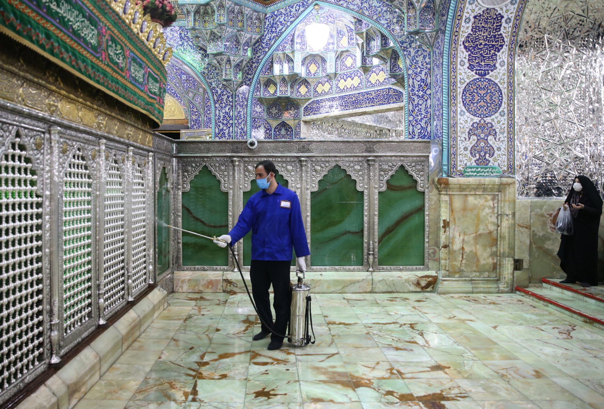 An Iranian sanitary worker disinfects Qom's Masoumeh shrine on 25 February 2020 to prevent the spread of the coronavirus (AFP)