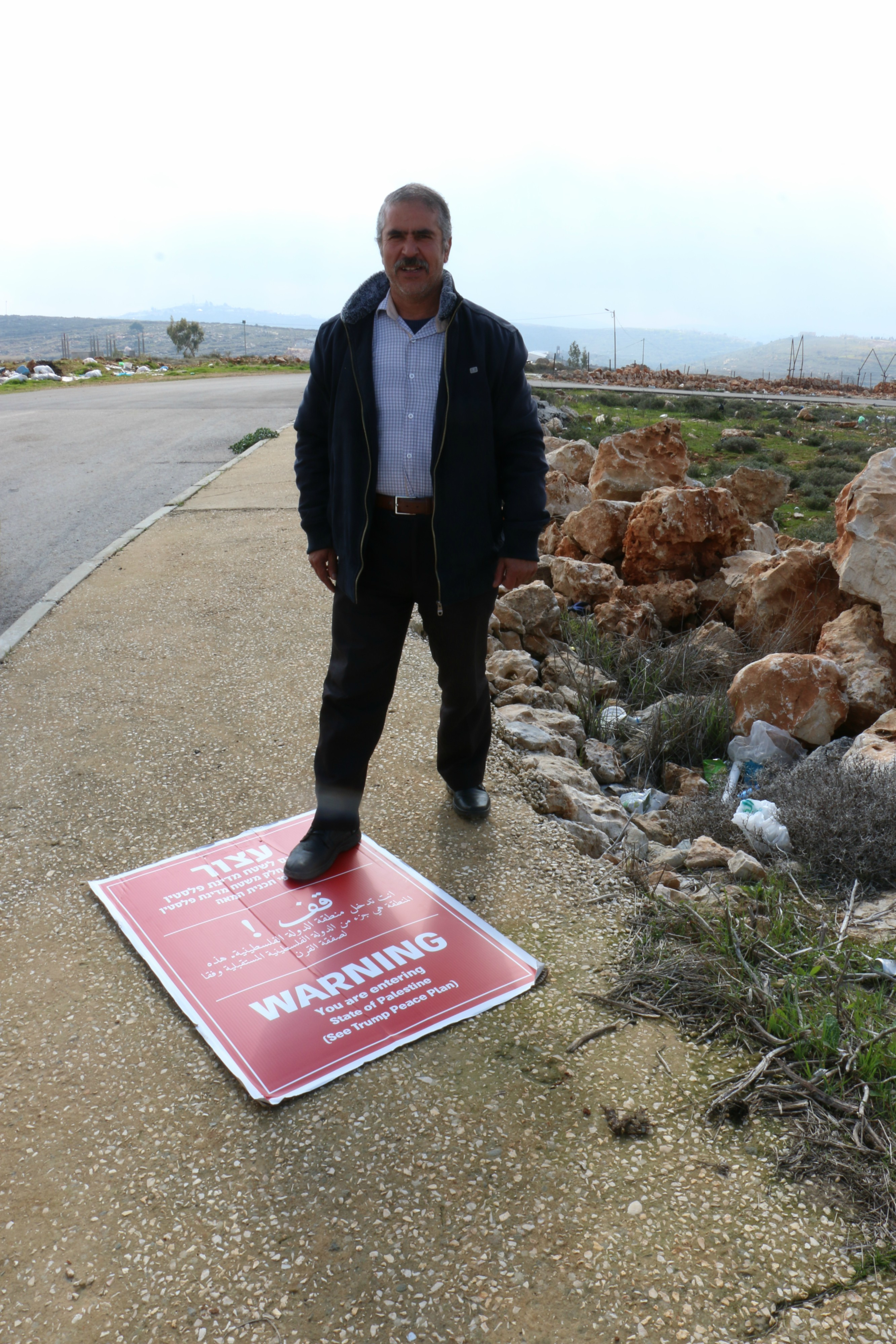 A resident of the village of Qusra steps on a Regavim sign (MEE/Akram al-Waara)