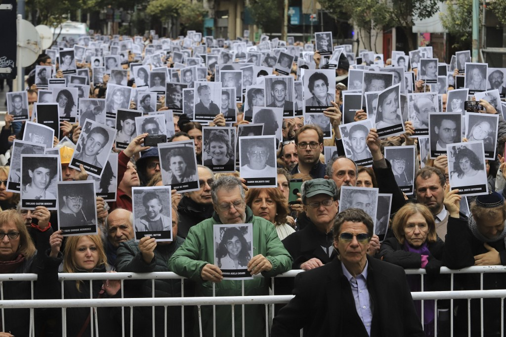 People hold pictures of the victims of the 1994 AMIA bombing during a commemoration in Buenos Aires on 18 July (Noticias Argentinas/AFP)