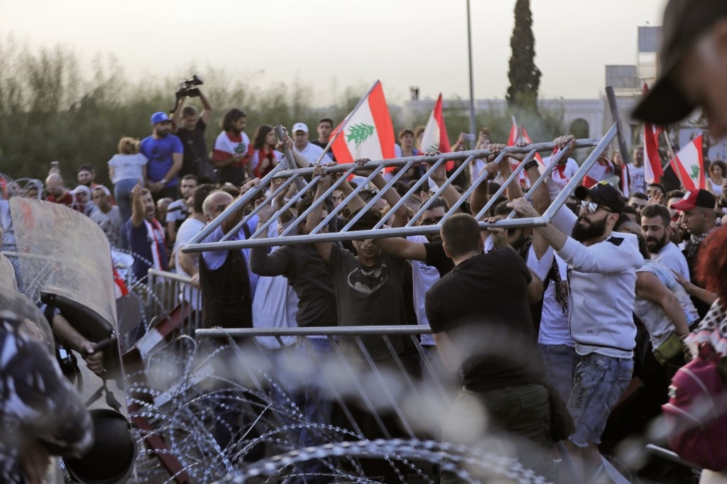Lebanese demonstrators try to remove the barbed-wire and metal rail, placed by anti-riot police, on the road leading to the Presidential Palace in Baabda on Wednesday (AFP)