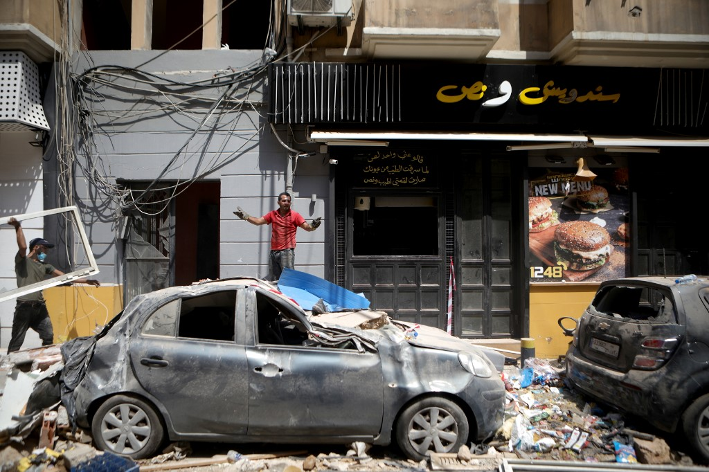 A man removes debris in Beirut's Mar Mikhael neighbourhood on 7 August (AFP)