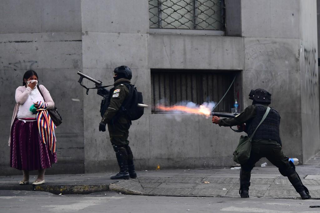 Bolivian riot police fire tear gas to disperse supporters of Morales, and locals discontented with the political situation, in La Paz on 13 November (AFP)