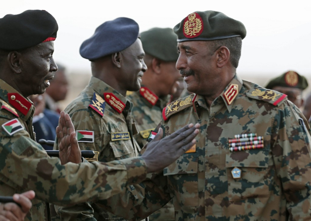 General Abdel Fattah al-Burhan greets military officers on the outskirts of Khartoum on 30 October (AFP)