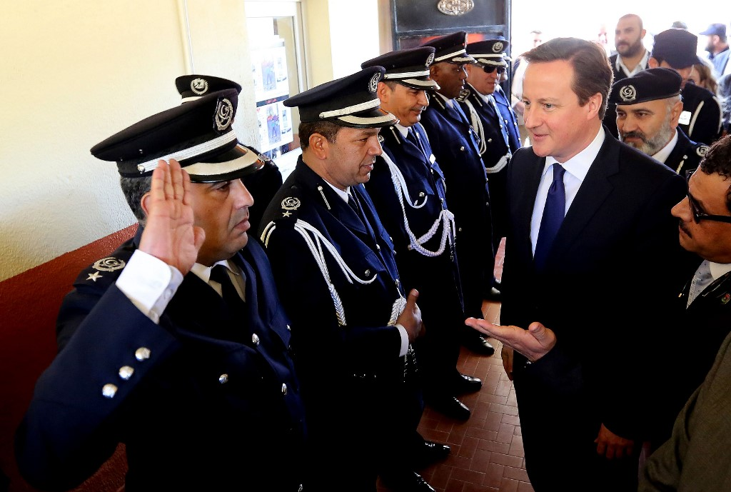 A Libyan police officer salutes Cameron in Tripoli in 2013 (AFP)