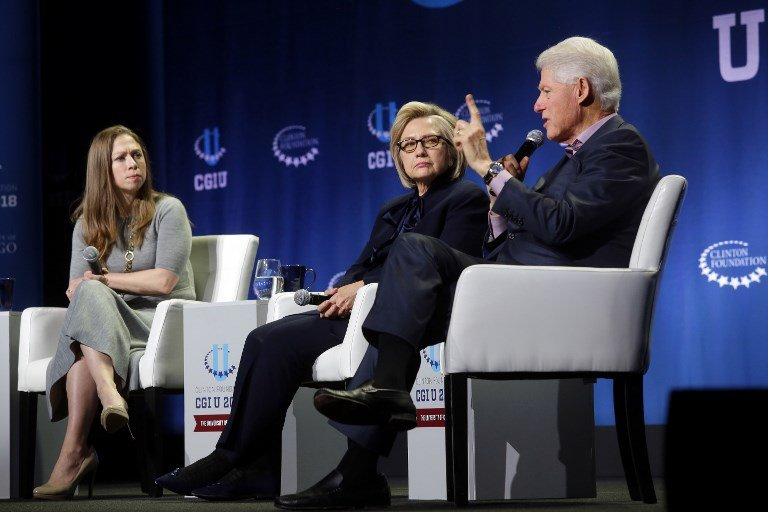 Hillary and Bill Clinton, and their daughter Chelsea, speak in Chicago on 16 October (AFP)