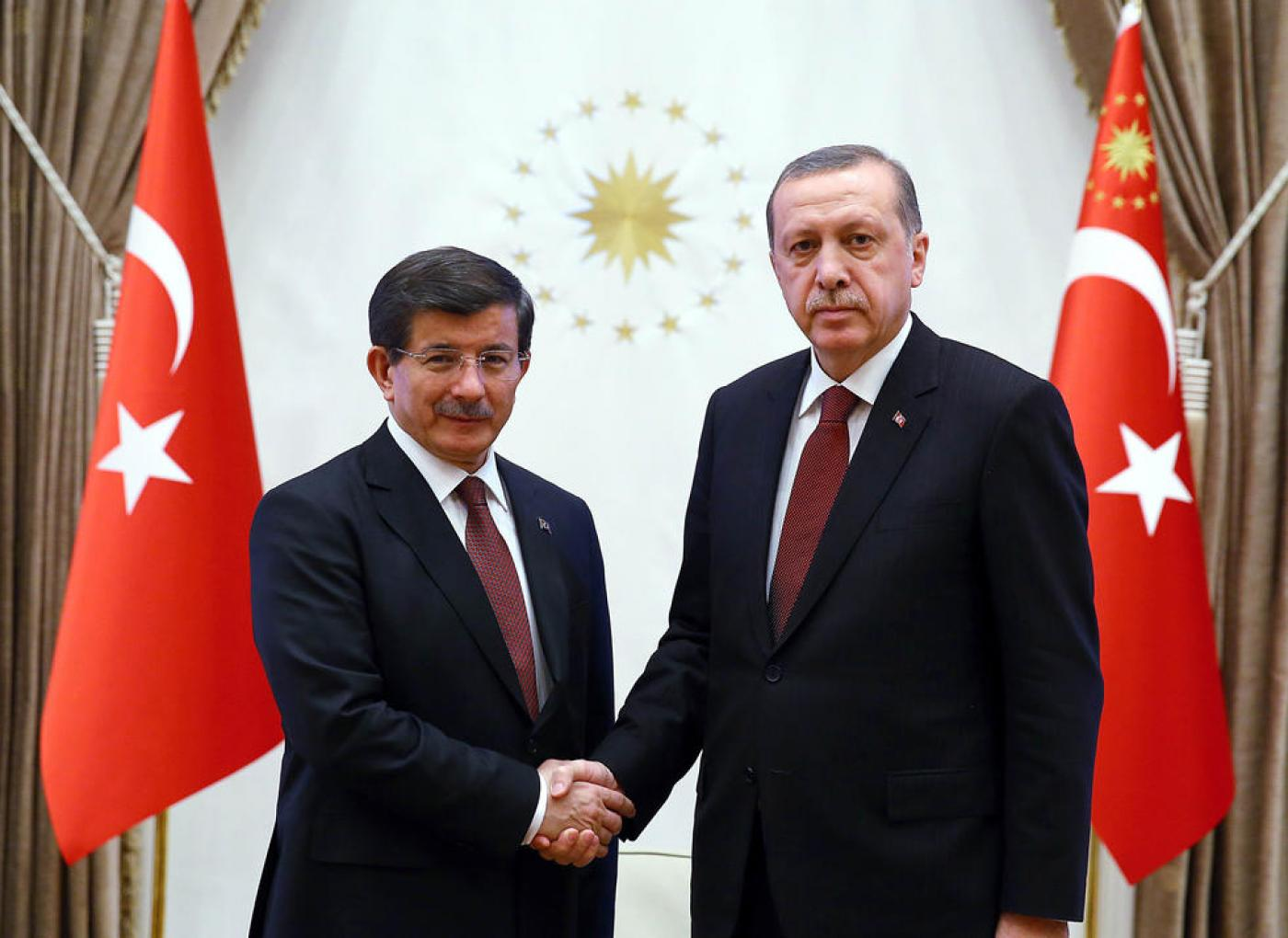 Turkish President Recep Tayyip Erdogan (R) shaking hands with Turkish Prime Minister Ahmet Davutoglu at Presidential Palace in Ankara on 29 January, 2015 (AFP/TURKISH PRESIDENTIAL PRESS OFFICE)