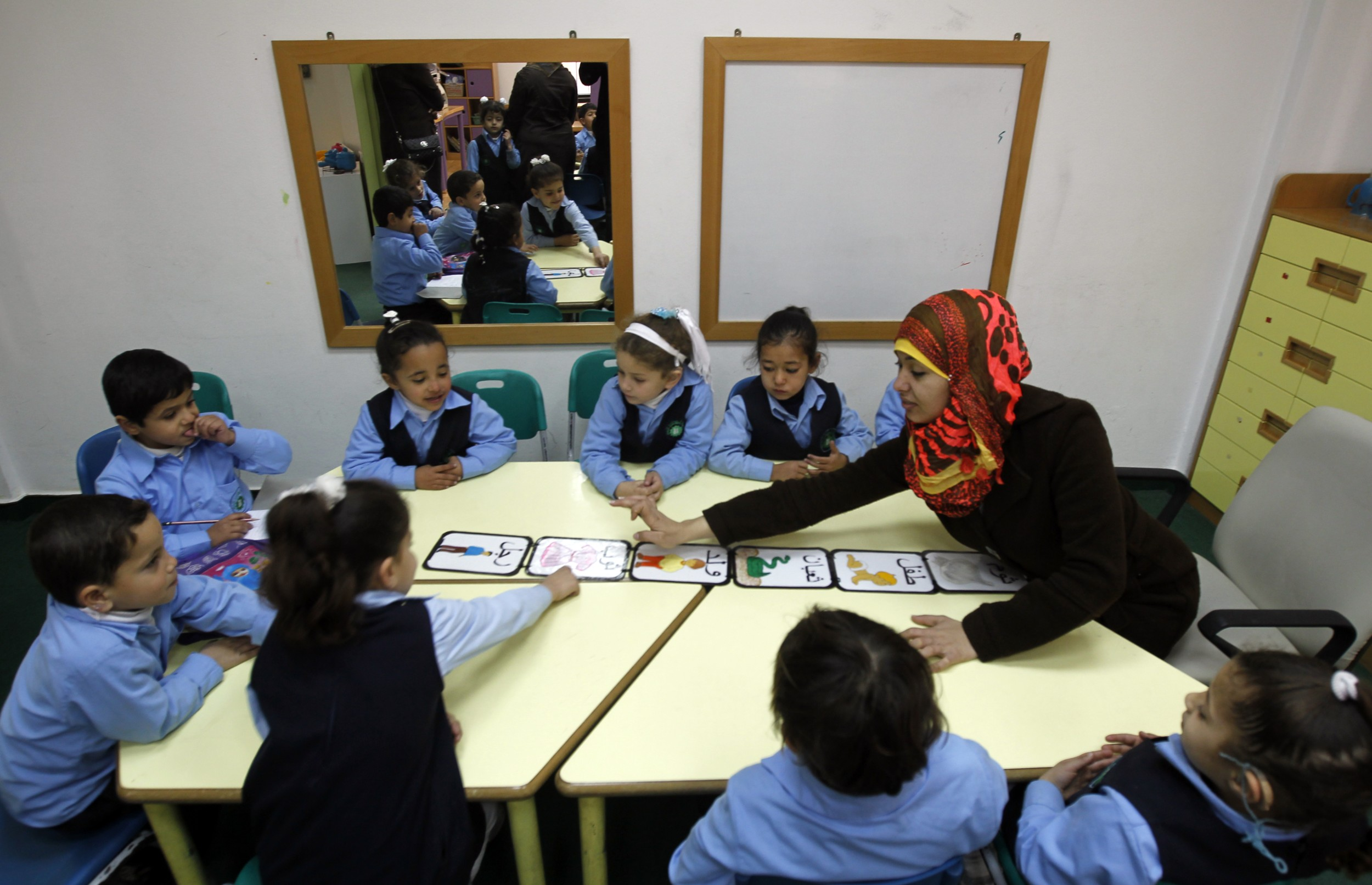 A deaf Palestinian woman teaches hearing impaired children at Atfaluna Society for Deaf Children in Gaza City, on 7 March 2013 (AFP)