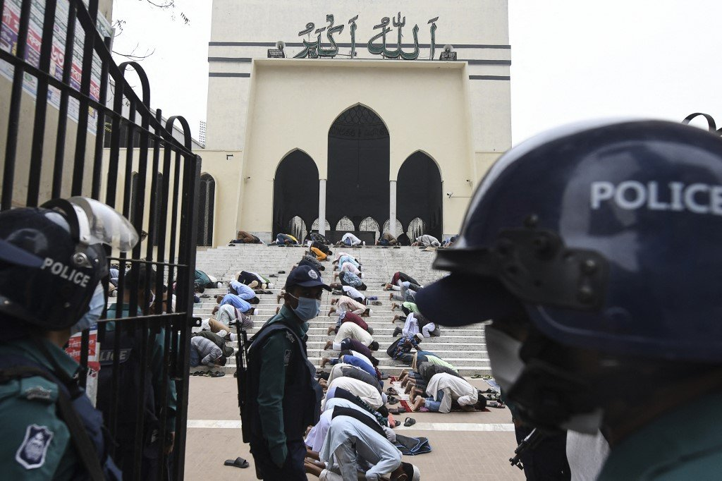 Police stand guard as Muslims pray at a Dhaka mosque on 11 December 2020 (AFP)