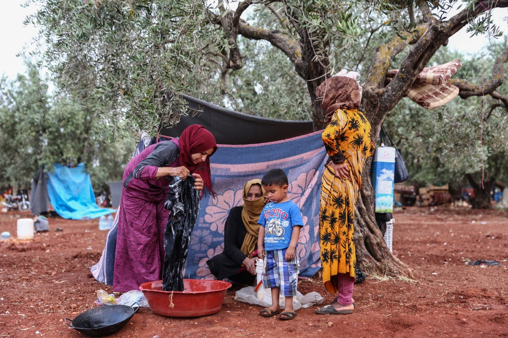 Displaced Syrian women wash clothes in a field in Idlib province on 23 May (AFP)